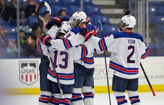 Team USA players mob teammate Cole Caufield (13) after one of his two goals Tuesday against Holy Cross.