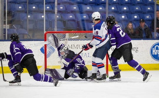 With Alex Turcotte (19) parked in front of Holy Cross goalie Erik Gordon (29), U.S. NTDP Under-18 player Cole Caufield (not shown) fires the puck into the net.