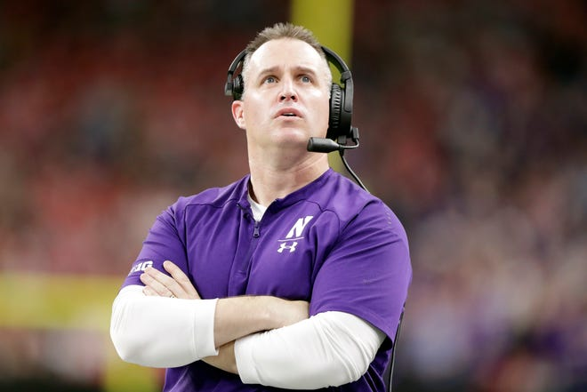 Northwestern head coach Pat Fitzgerald watches a replay of running back John Moten IV touchdown run during the first half of the Big Ten championship NCAA college football game against Ohio State, Saturday, Dec. 1, 2018, in Indianapolis. (AP Photo/Michael Conroy)