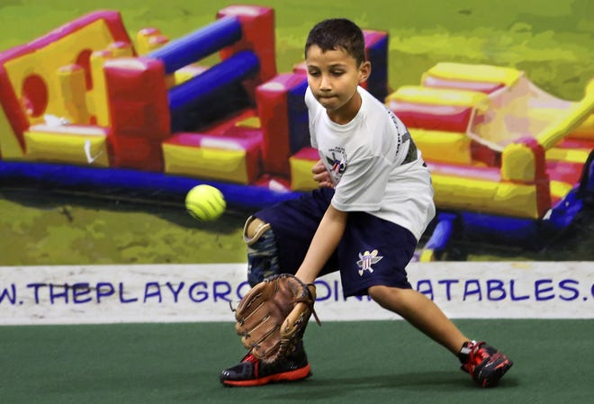 Adrian Grajeda works on his fielding at a Wounded Warrior Clinic for kids in June 2014, in Louisville, Ky.