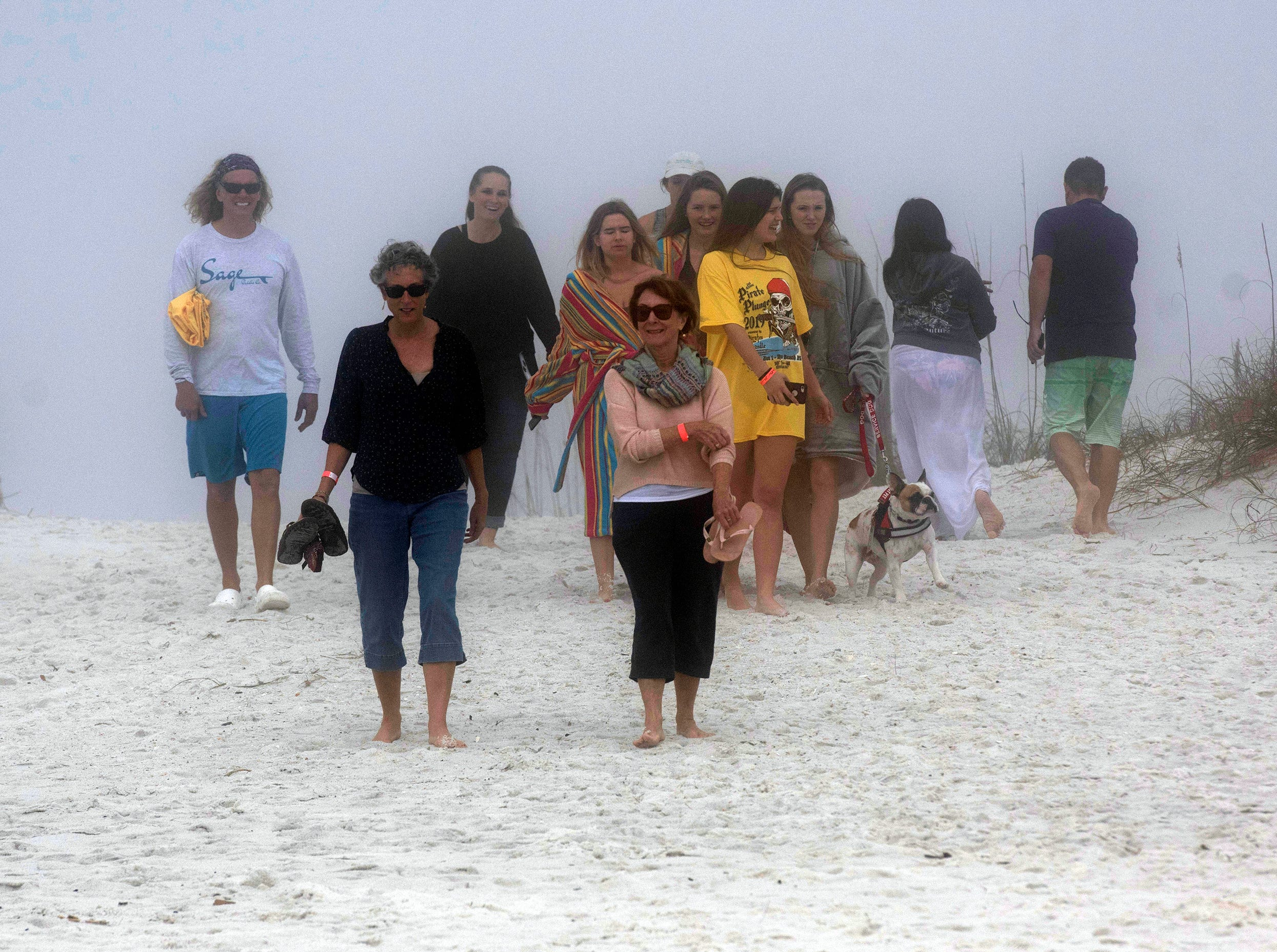 """Hundreds of thrill seekers all ages gathered on a foggy Navarre Beach Tuesday, Jan. 1, 2019 to take part in the 2nd annual Pirate Plunge. The New Year's Day activity put on by the Pirates of the Panhandle Social Club drew an estimated crowd over 450 people, organizer, """"Jersey"""" Jerry Foster said. The event benefits the Weekend Food Program of Navarre."""