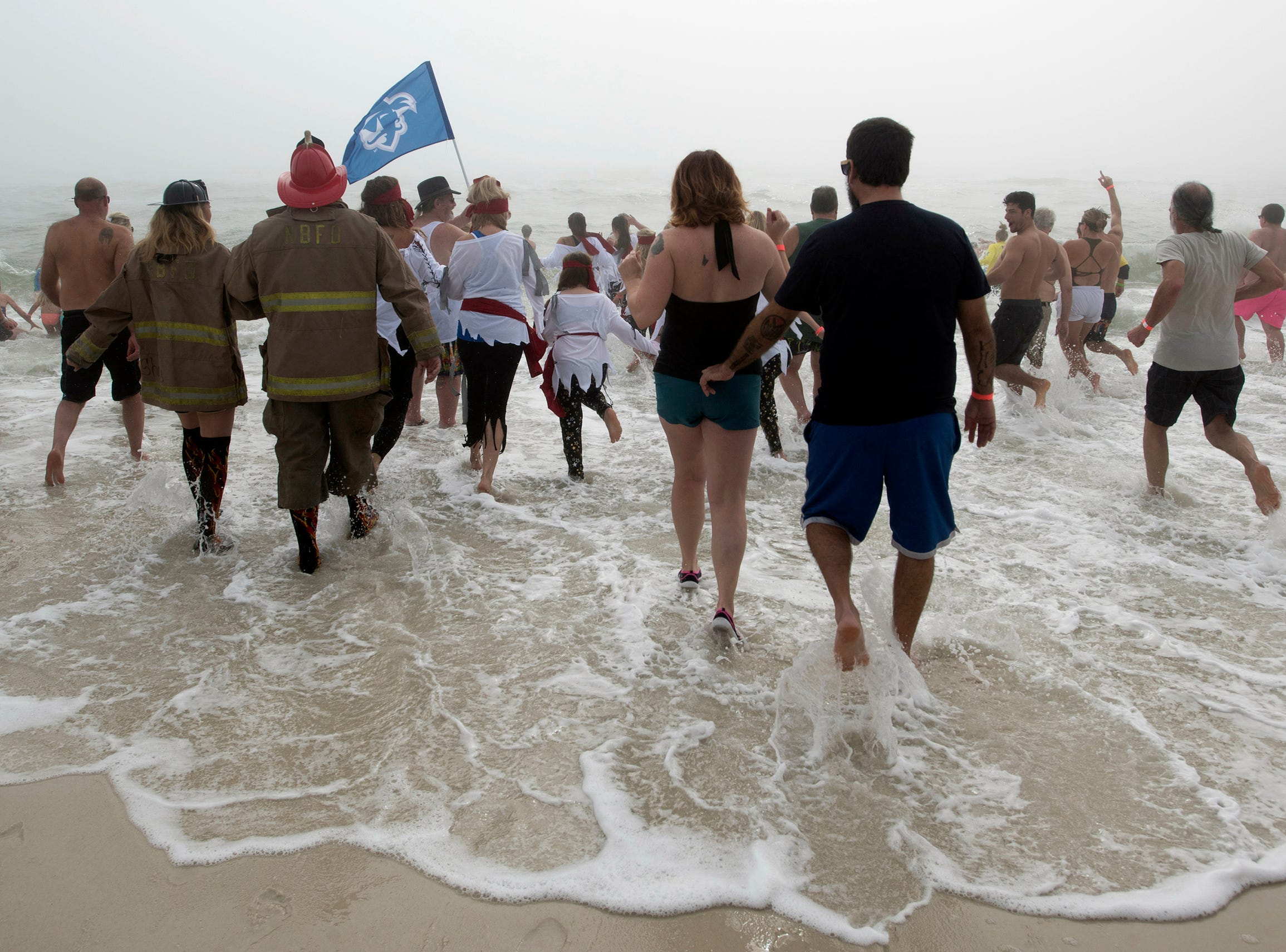 """Pirates and pirate wanna-a-bees prepare to take a dip in the cold waters of the Gulf of Mexico during the 2nd annual Pirate Plunge on Tuesday, Jan.1, 2019. The New Year's Day activity put on by the Pirates of the Panhandle Social Club drew an estimated crowd over 450 people, said organizer, """"Jersey"""" Jerry Foster."""