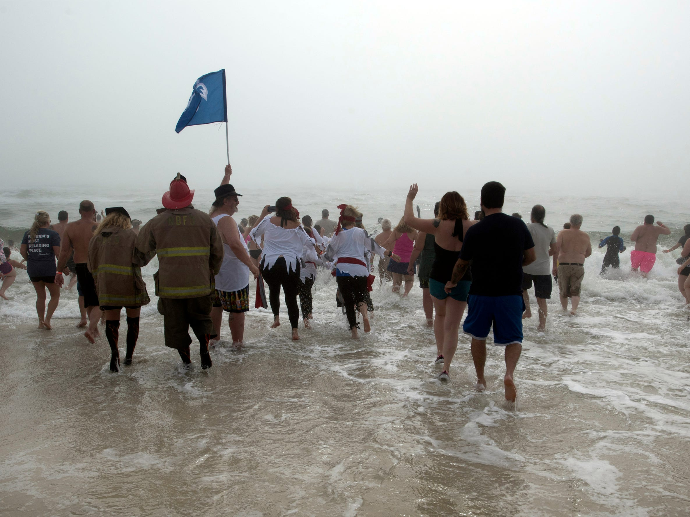 """""""Jersey"""" Jerry Foster, holding a flag, leads a group of pirates and pirate wanna-a-bees into the cold and foggy waters of the Gulf of Mexico during the 2nd annual Navarre Beach Pirate Plunge on Tuesday, Jan.1, 2019."""