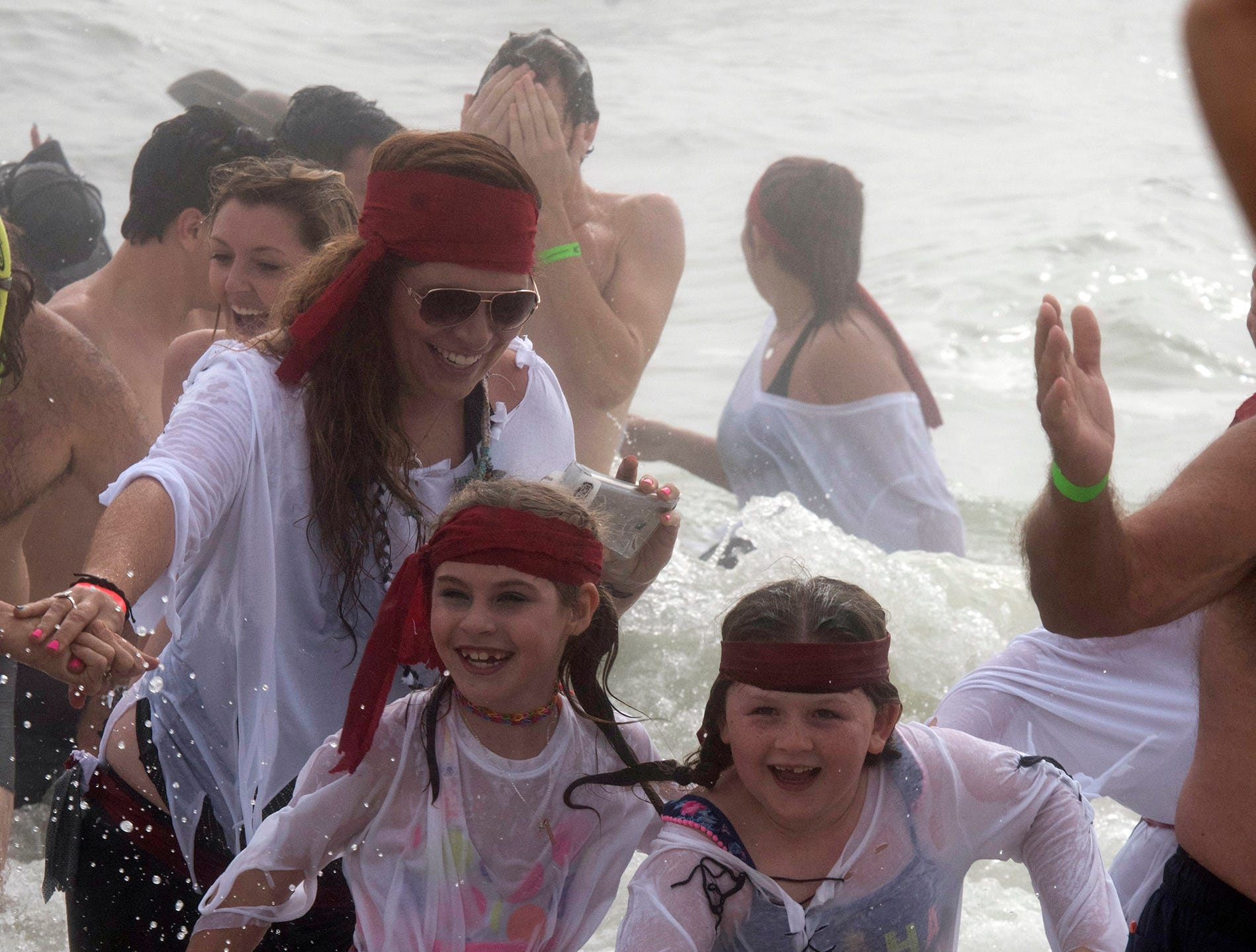 """Pirates and pirate wanna-a-bees of all ages take a dip in the cold and foggy waters of the Gulf of Mexico during the 2nd annual Navarre Beach Pirate Plunge on Tuesday, Jan.1, 2019. The New Year's Day activity put on by the Pirates of the Panhandle Social Club drew an estimated crowd over 450 people, said organizer, """"Jersey"""" Jerry Foster."""