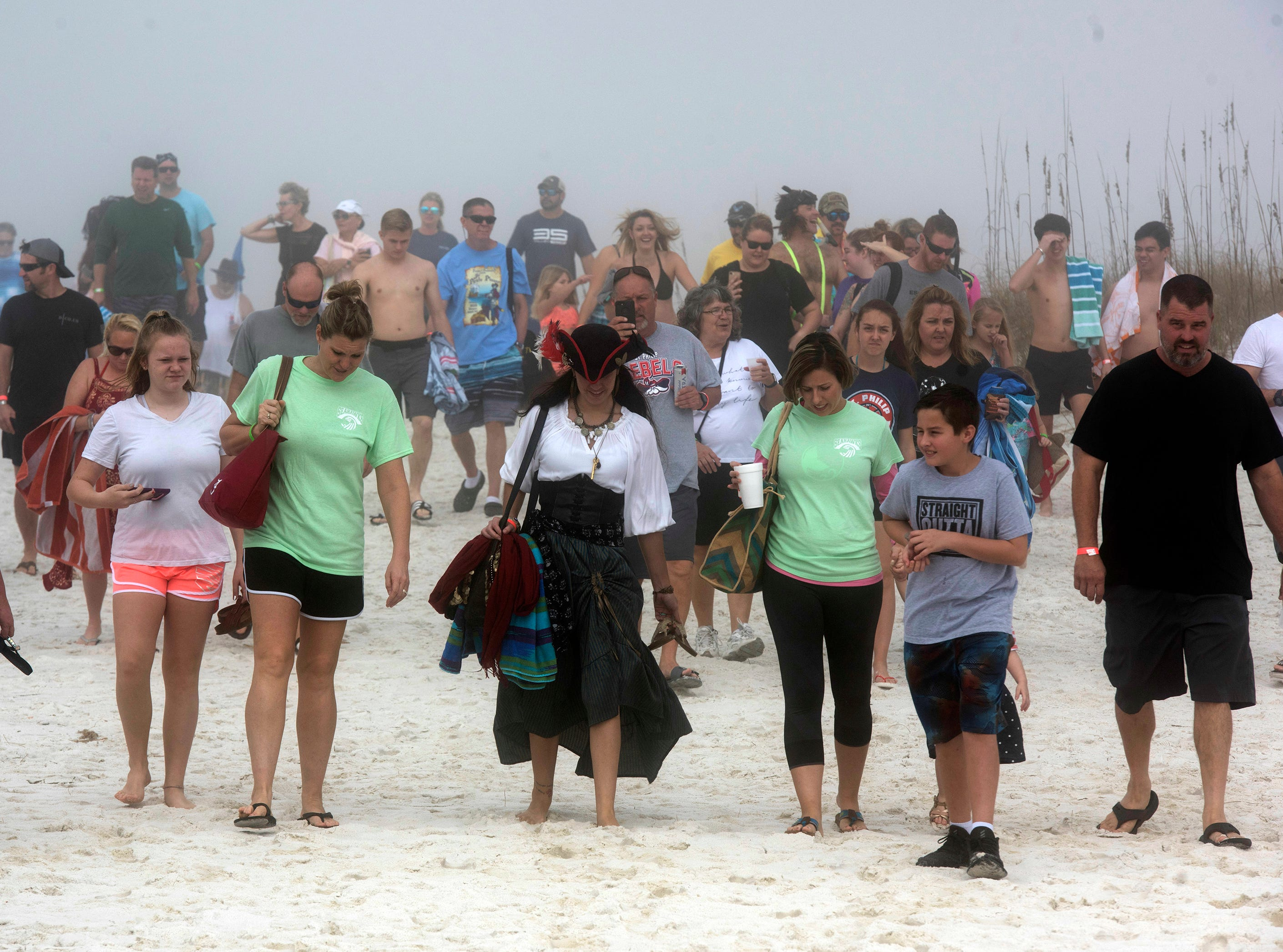 """Hundreds of thrill seekers all ages gathered on a foggy Navarre Beach Tuesday, Jan. 1, 2019 to take part in the 2nd annual Pirate Plunge. The New Year's Day activity put on by the Pirates of the Panhandle Social Club drew an estimated crowd over 450 people, organizers, """"Jersey"""" Jerry Foster said. The event benefits the Weekend Food Program of Navarre."""