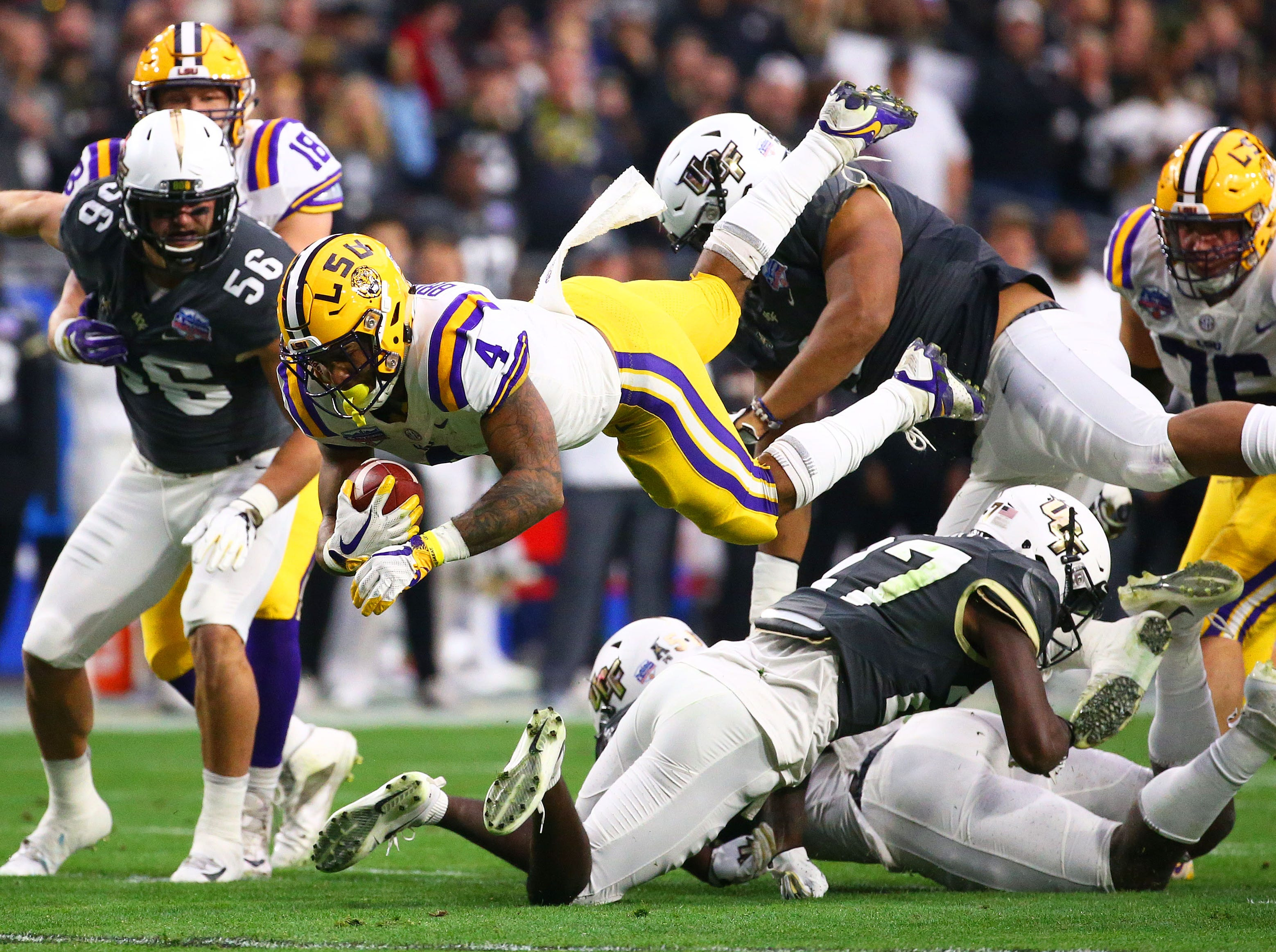 LSU Tigers running back Nick Brossette (4) dives over the UCF Knights defensive in the first half at the Fiesta Bowl on Jan. 1 at State Farm Stadium.
