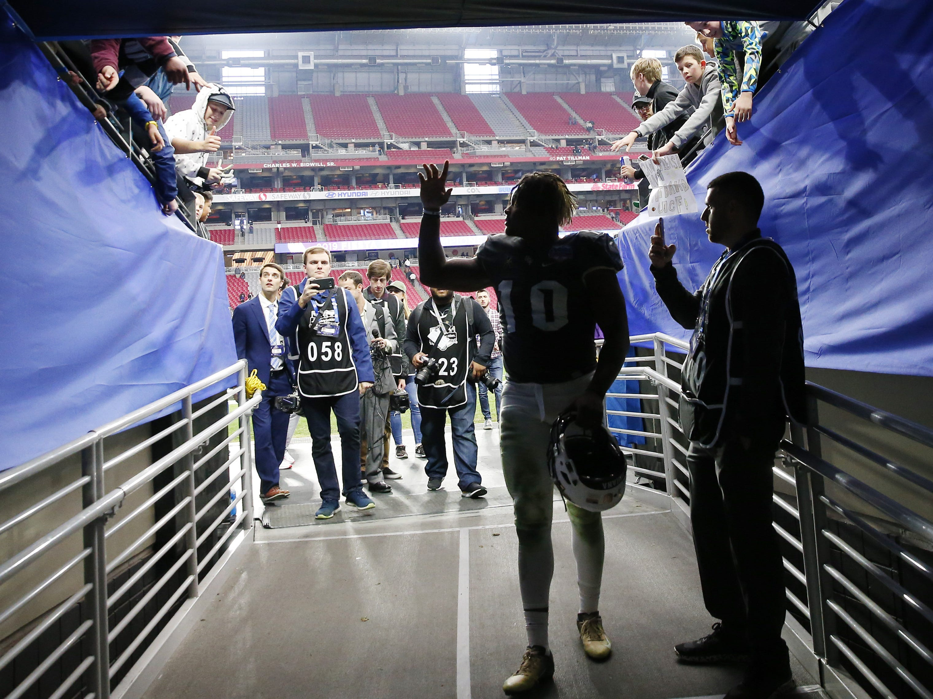 UCF defensive lineman Titus Davis (10) waves to fans while walking off the field after losing to LSU in the Fiesta Bowl in Glendale January 1, 2019. LSU won 40-32.