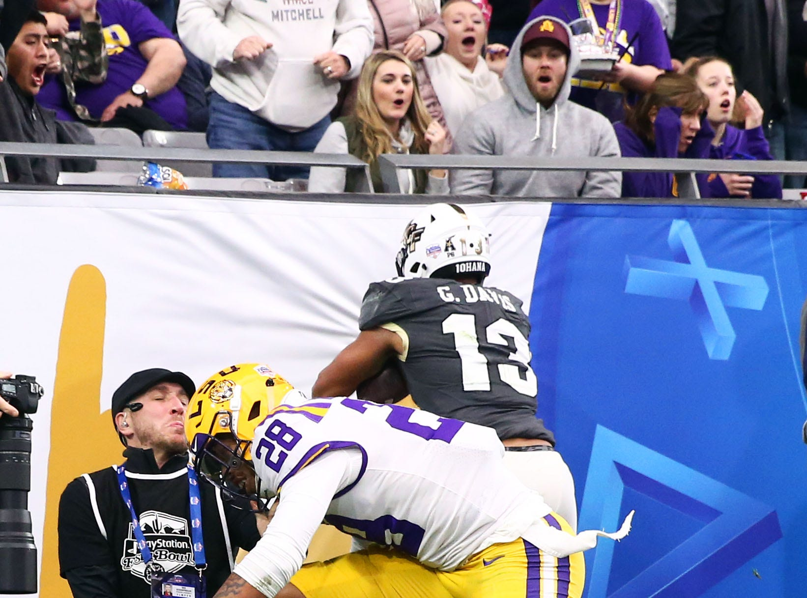 LSU Tigers corner back Mannie Netherly (28) takes-out a cameraman as UCF Knight wide receiver Gabriel Davis (13) makes a touchdown catch in the first half at the Fiesta Bowl on Jan. 1 at State Farm Stadium.