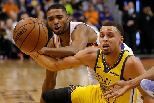 Golden State Warriors guard Stephen Curry, right, and Phoenix Suns forward Mikal Bridges vie for the ball during the first half of an NBA basketball game Monday, Dec. 31, 2018, in Phoenix. (AP Photo/Rick Scuteri)