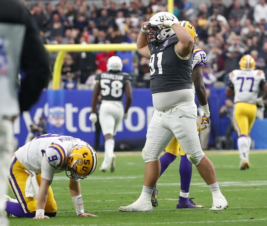UCF defensive lineman Joey Connors (91) flexes after hitting LSU quarterback Joe Burrow (9) after an interception and touchdown during the Fiesta Bowl in Glendale January 1, 2019.