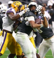 LSU Tigers linebacker Jacob Phillips (6) grabs the face mask of UCF Knights quarterback Darriel Mack Jr. in the second half at the Fiesta Bowl on Jan. 1 at State Farm Stadium.