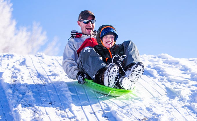 Tadd Fagerud and his son, Sawyer, 5, Payson, hollar with delight as they slide down a hill in fresh snowfall at Green Valley Park in Payson on New Year's Day, 2019.