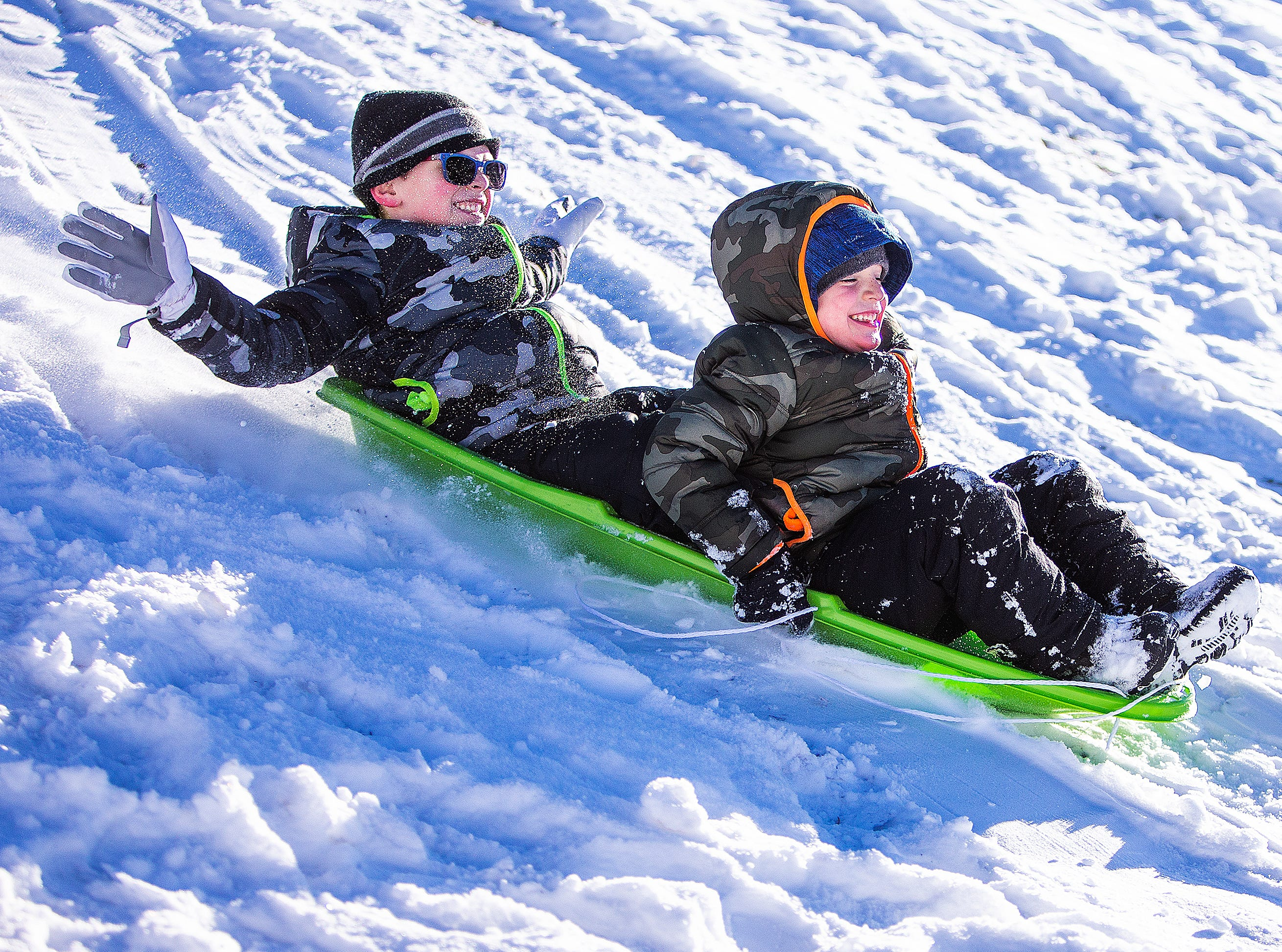 Kade Fagerud, 6, left, and his brother, Sawyer, 5, Payson, slide with delight down a hill on fresh snowfall at Green Valley Park in Payson on New Year's Day, 2019.