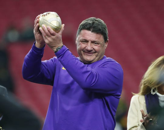 LSU football coach Ed Orgeron holds up on the Fiesta Bowl trophy after beating UCF on Jan. 1.