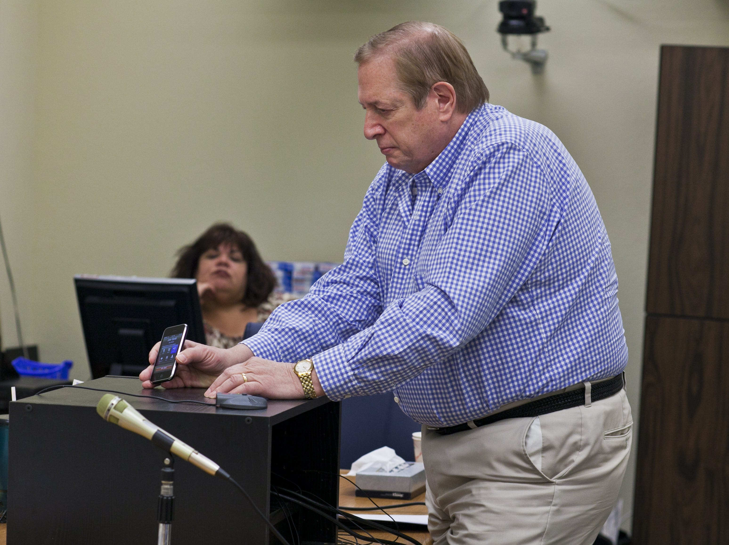 Sanford Kane, father of murder victim Eric Kane, holds up an iPhone so Jon Gold can speak against paroling Eric's killer, Jacob Wideman, at the Arizona Board of Executive Clemency (Parole Board) in May 2011 in Phoenix.