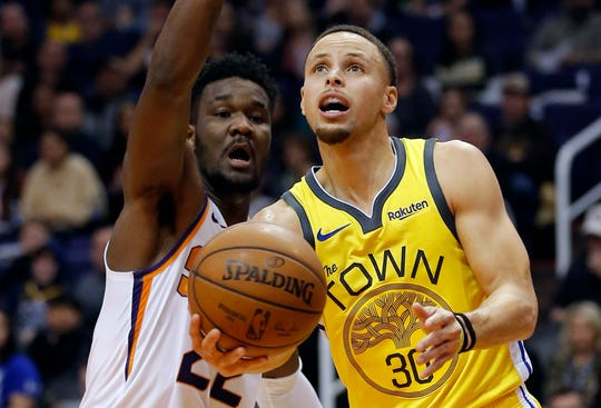 Golden State Warriors guard Stephen Curry (30) drives past Phoenix Suns center Deandre Ayton during the first half of an NBA basketball game Monday, Dec. 31, 2018, in Phoenix. (AP Photo/Rick Scuteri)