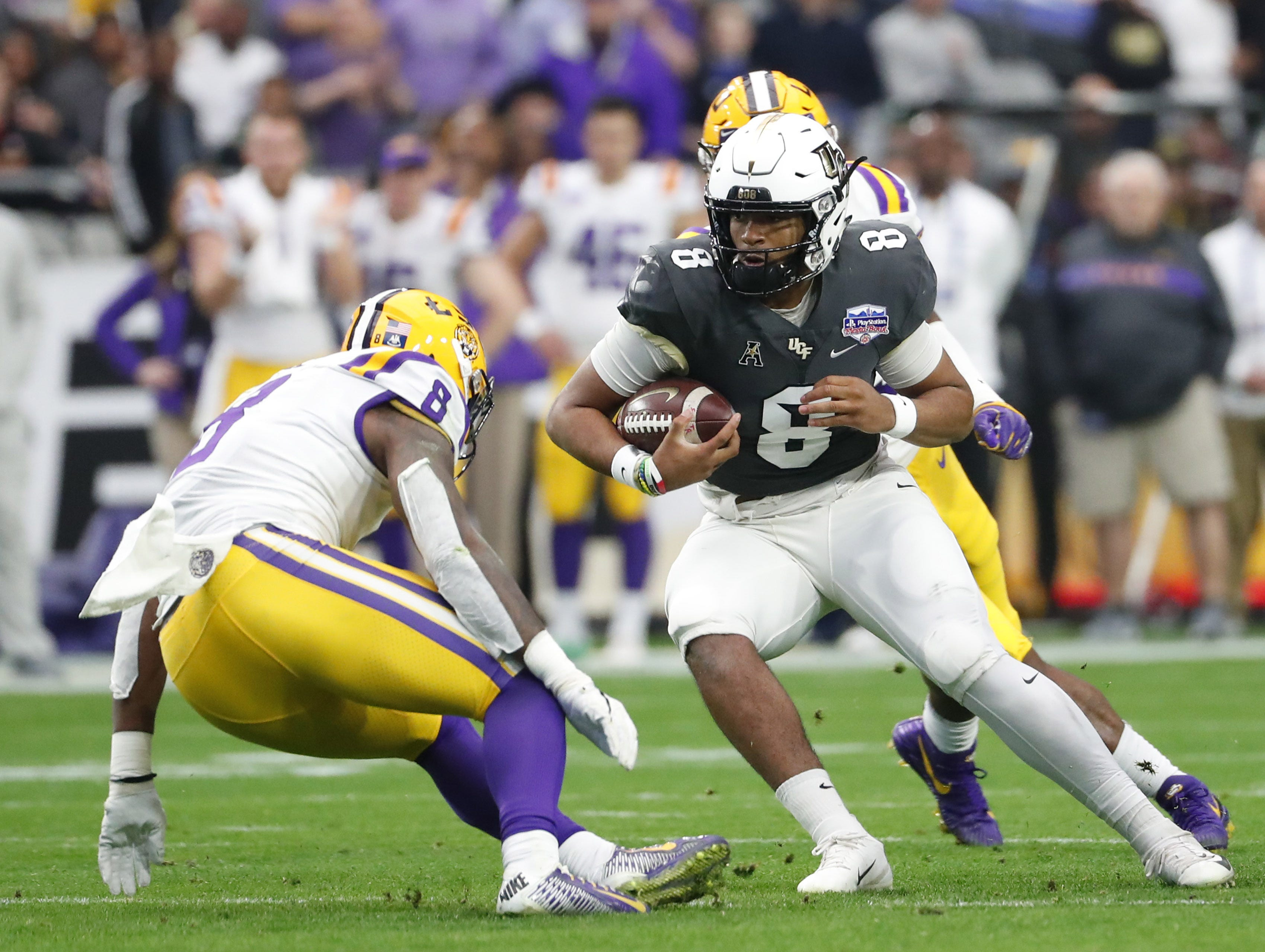UCF quarterback Darriel Mack Jr. (8) puts a move on LSU linebacker Patrick Queen (8) during the Fiesta Bowl in Glendale January 1, 2019.