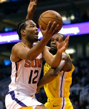 Phoenix Suns forward T.J. Warren (12) drives by Golden State Warriors forward Kevin Durant during the second half during an NBA basketball game Monday, Dec. 31, 2018, in Phoenix. Golden State defeated the Suns 132-109. (AP Photo/Rick Scuteri)