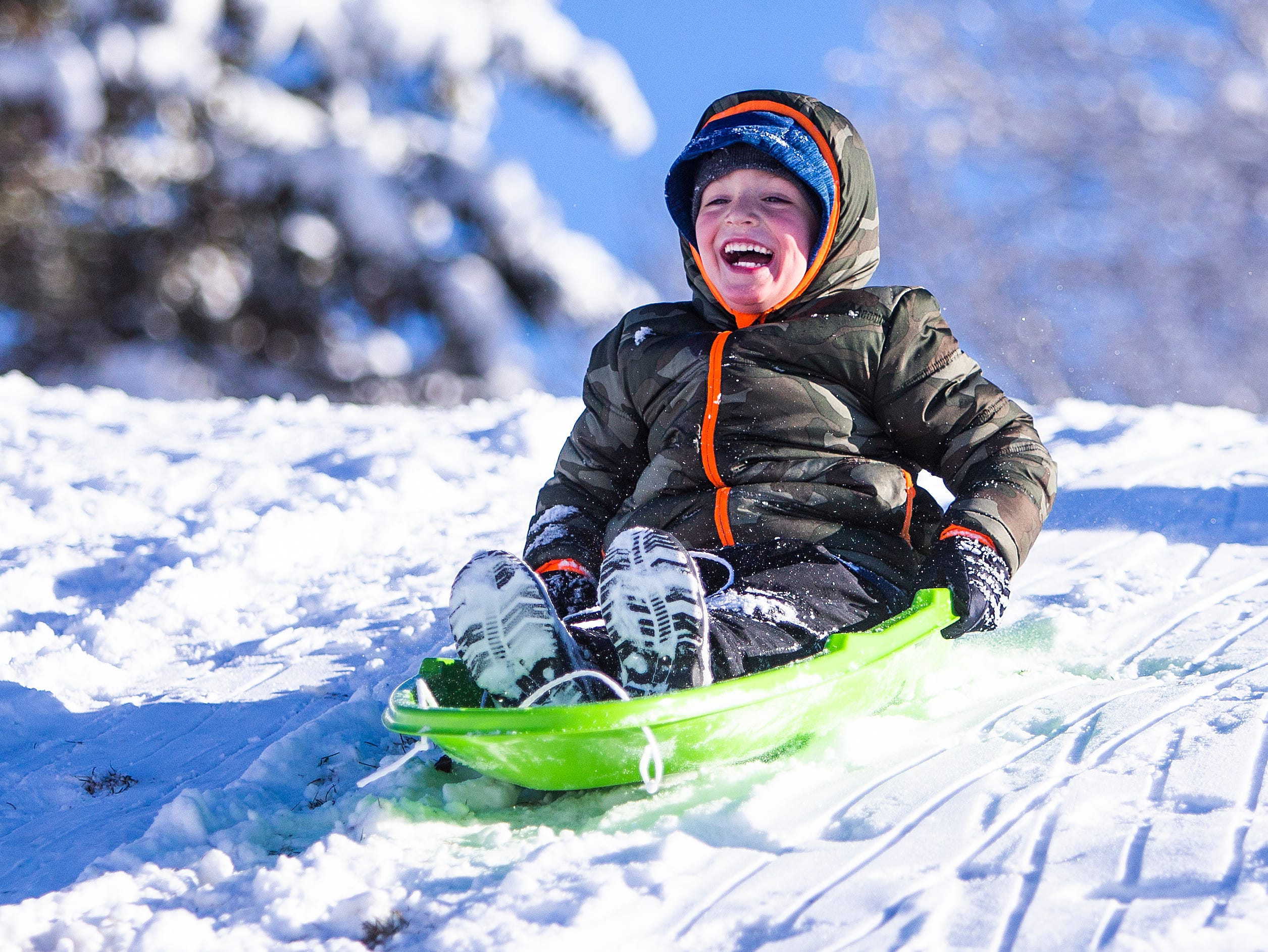 Sawyer Fagerud, 5, Payson, squeals with delight as he slides down a hill in fresh snowfall at Green Valley Park in Payson on New Year's Day, 2019.
