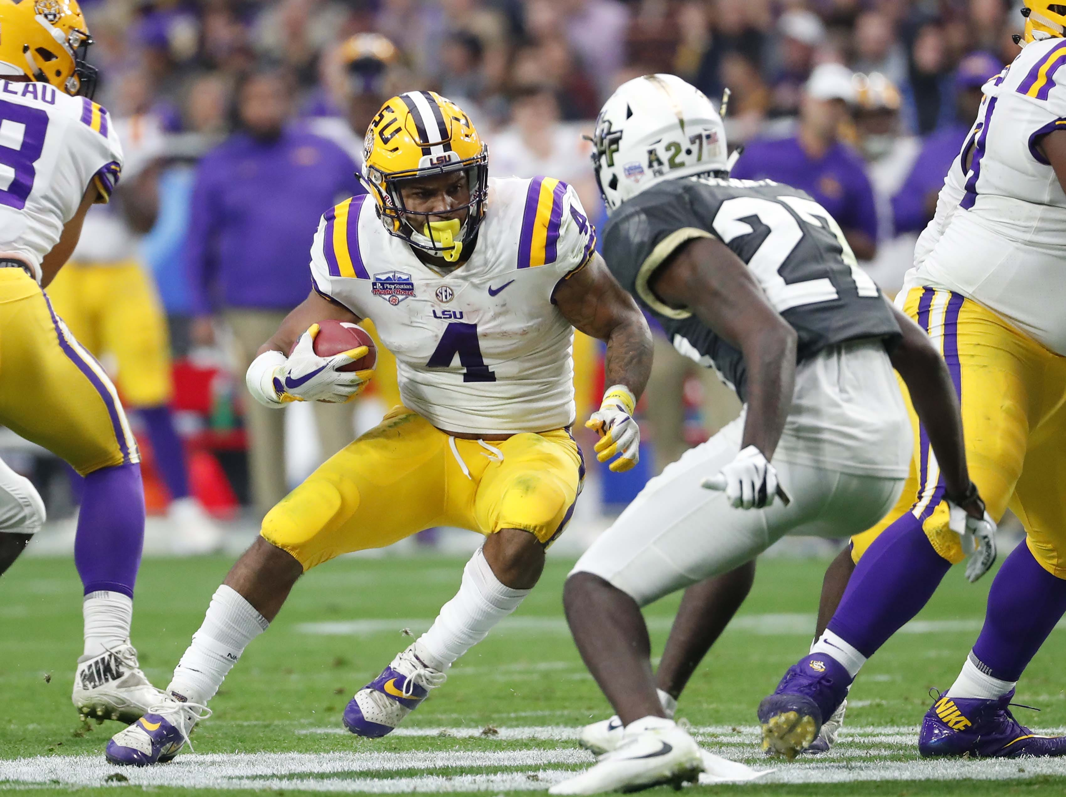 LSU running back Nick Brossette (4) runs against UCF defensive back Richie Grant (27) during the Fiesta Bowl in Glendale January 1, 2019.