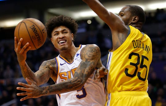 Phoenix Suns forward Kelly Oubre Jr. gets fouled by Golden State Warriors forward Kevin Durant (35) during the second half of an NBA basketball game Monday, Dec. 31, 2018, in Phoenix. Golden State defeated the Suns 132-109. (AP Photo/Rick Scuteri)