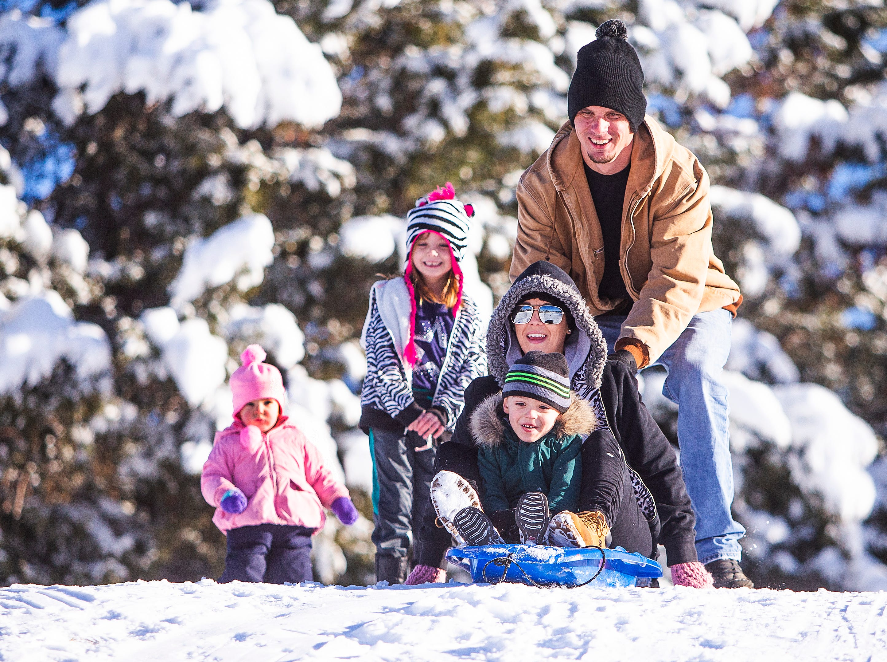 James Papa of Phoenix pushes his wife, Ashley, and son, Dylan, 4, down a hill on fresh snowfall at Green Valley Park in Payson on New Year's Day, 2019.