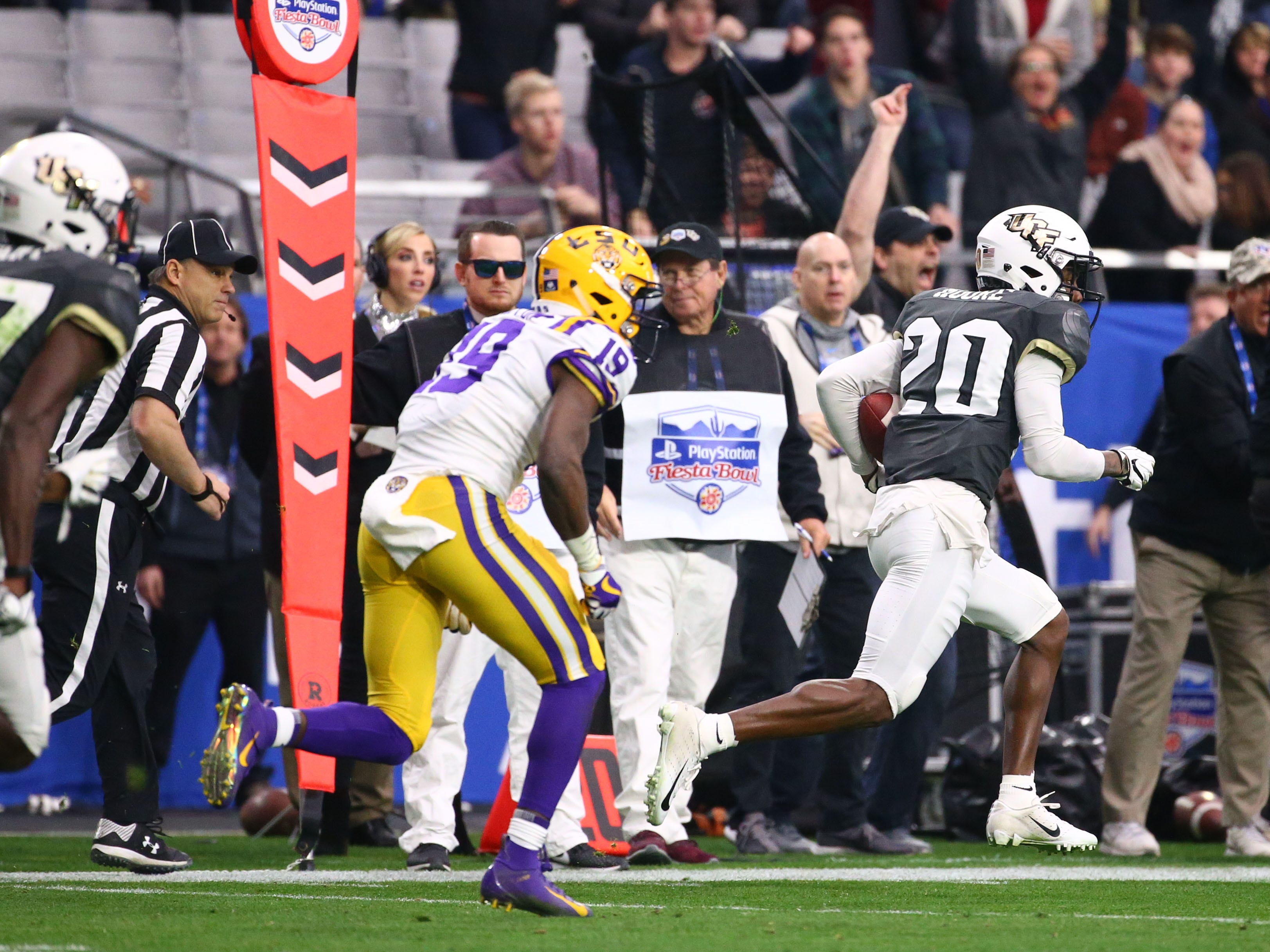 UCF Knights defensive back Brandon Moore (20) scores a touchdown on a interception against the LSU Tigers in the first half at the Fiesta Bowl on Jan. 1 at State Farm Stadium.