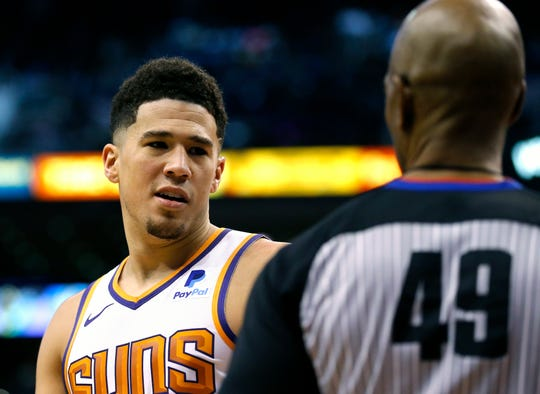 Phoenix Suns guard Devin Booker (1) talks to NBA official Tom Washington after committing a foul against the Golden State Warriors during the second half of an NBA basketball game, Monday, Dec. 31, 2018, in Phoenix. Golden State defeated the Suns 132-109. (AP Photo/Rick Scuteri)
