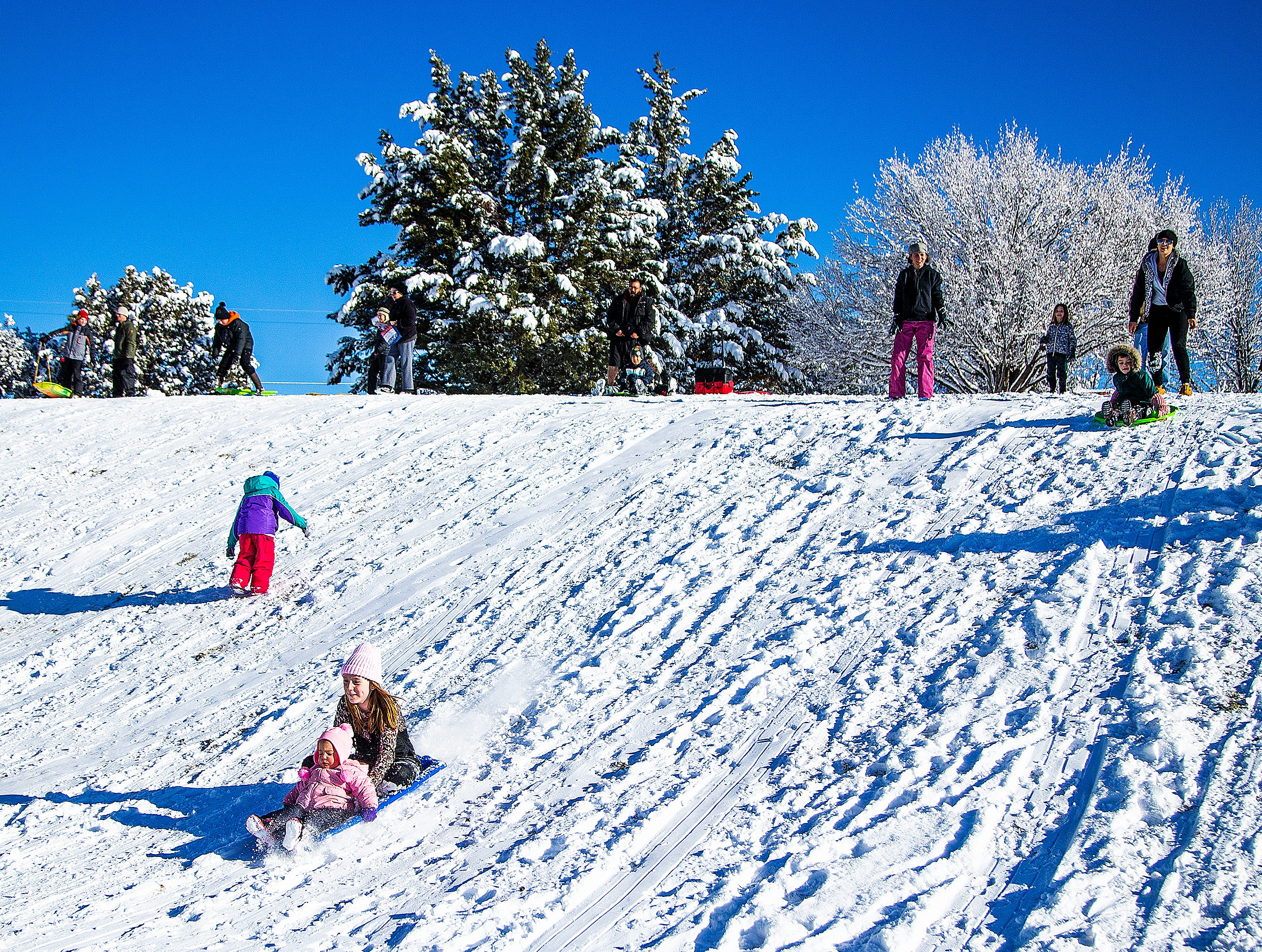 Families take advantage of fresh snowfall to slide down a hill at Green Valley Park in Payson on New Year's Day, 2019.