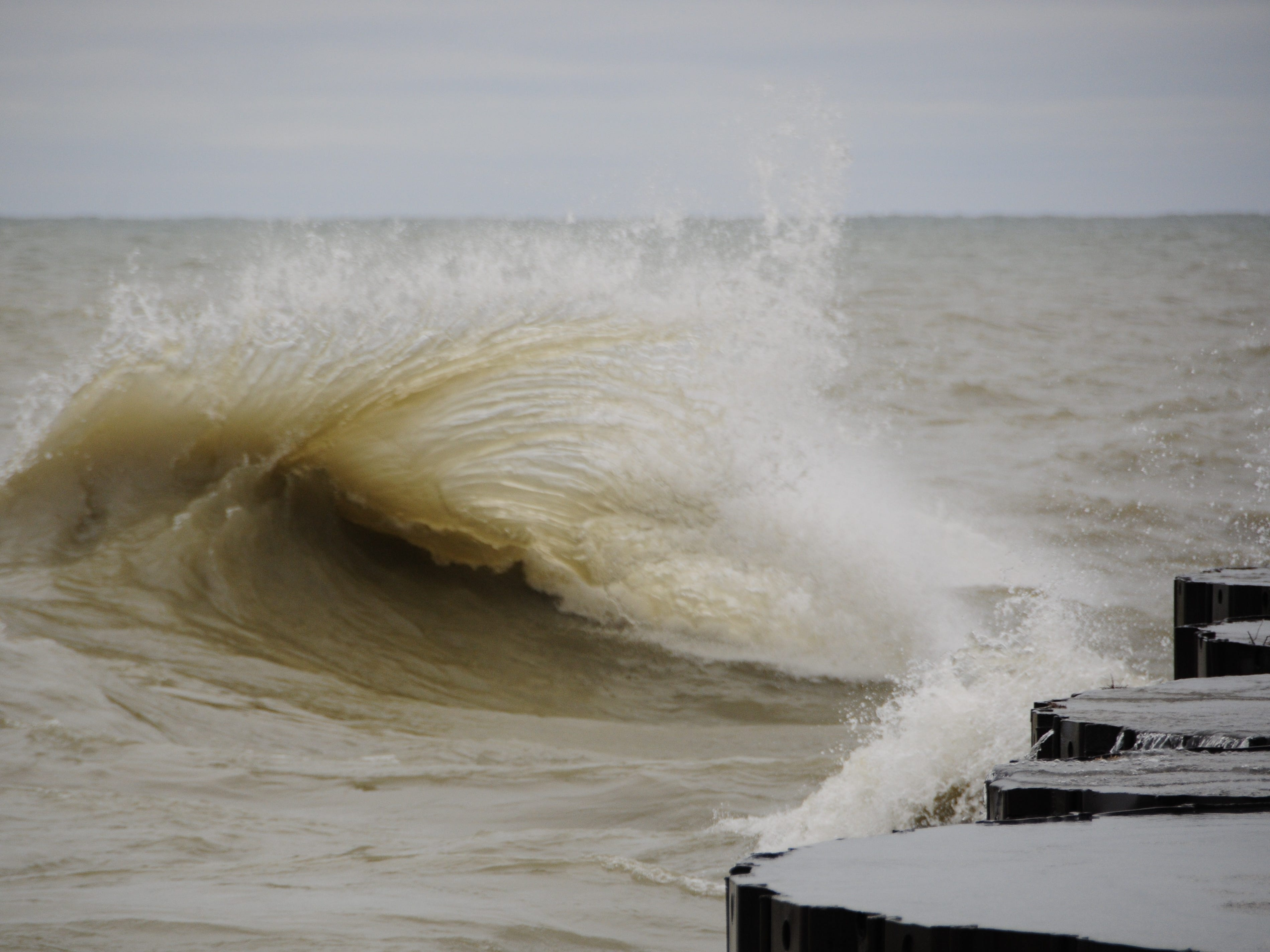 A wave erupts into tentacle-like streamers in Port Sanilac on New Year's Day 2019.