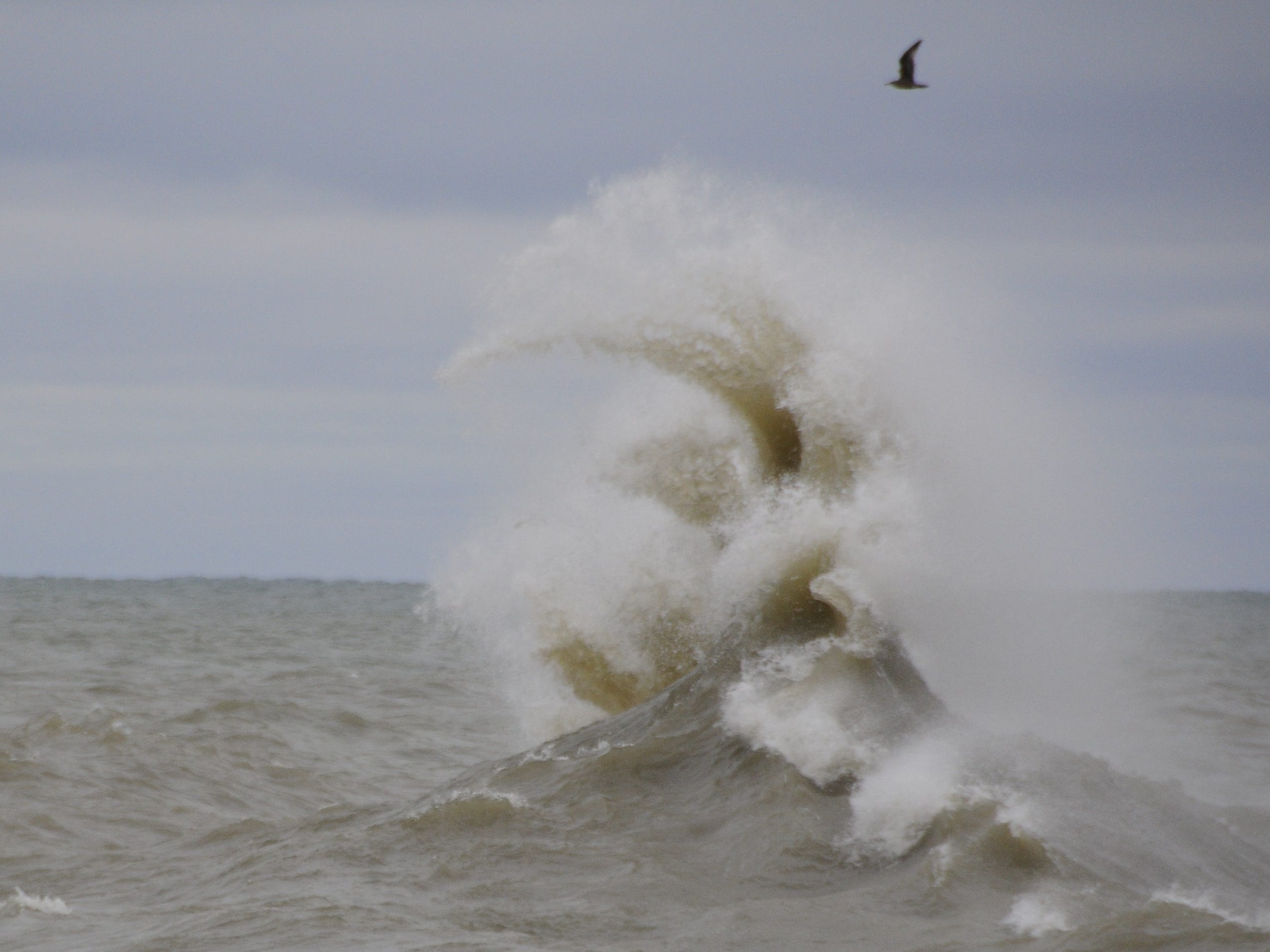 Waves collide, sending water jetting into the air in Port Sanilac on New Year's Day 2019.