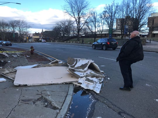 Poughkeepsie Grand Hotel co-owner Joe Bonura inspects damage to the hotel's facade Tuesday morning.