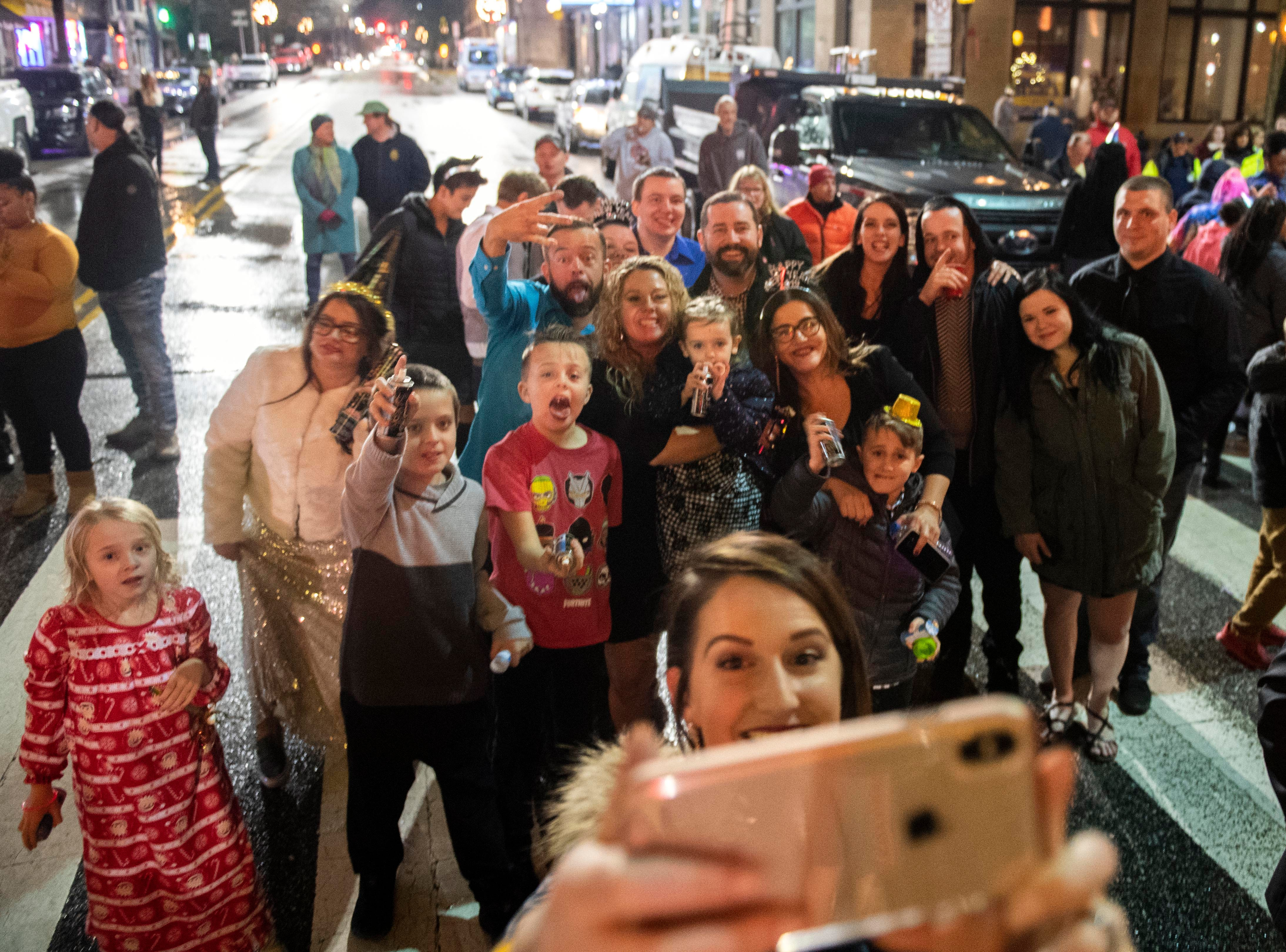 A group poses for a photo prior to the white rose dropping to ring in the new year in Continental Square downtown, Monday, Dec. 31, 2018. Hundreds gathered to watch the white rose drop, dance and ring in the new year.