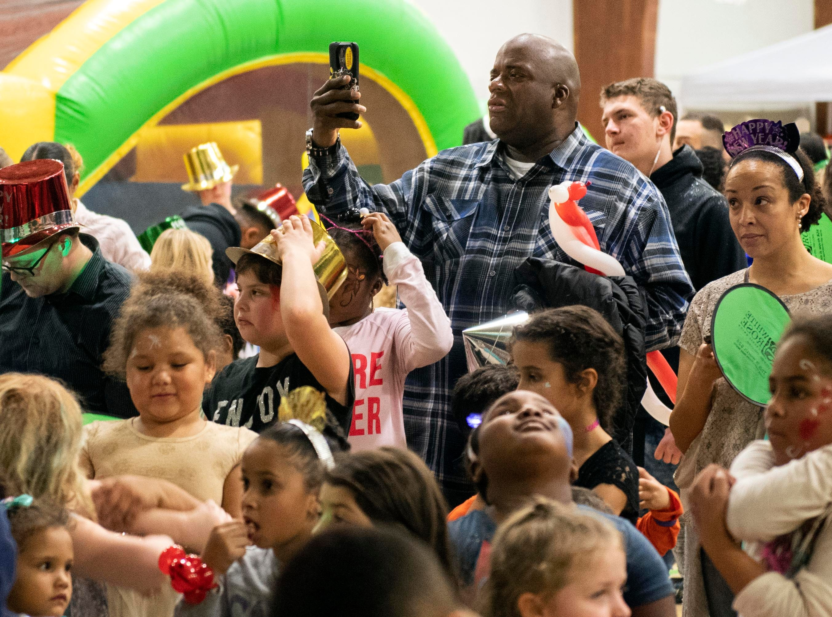 Parents watch on prior to the balloon drop during the Children's Countdown to 2019 event at Voni Grimes Gym, Monday, Dec. 31, 2018. Hundreds of kids rang in the new year early, along with getting their faces painted, dancing and bounce houses.