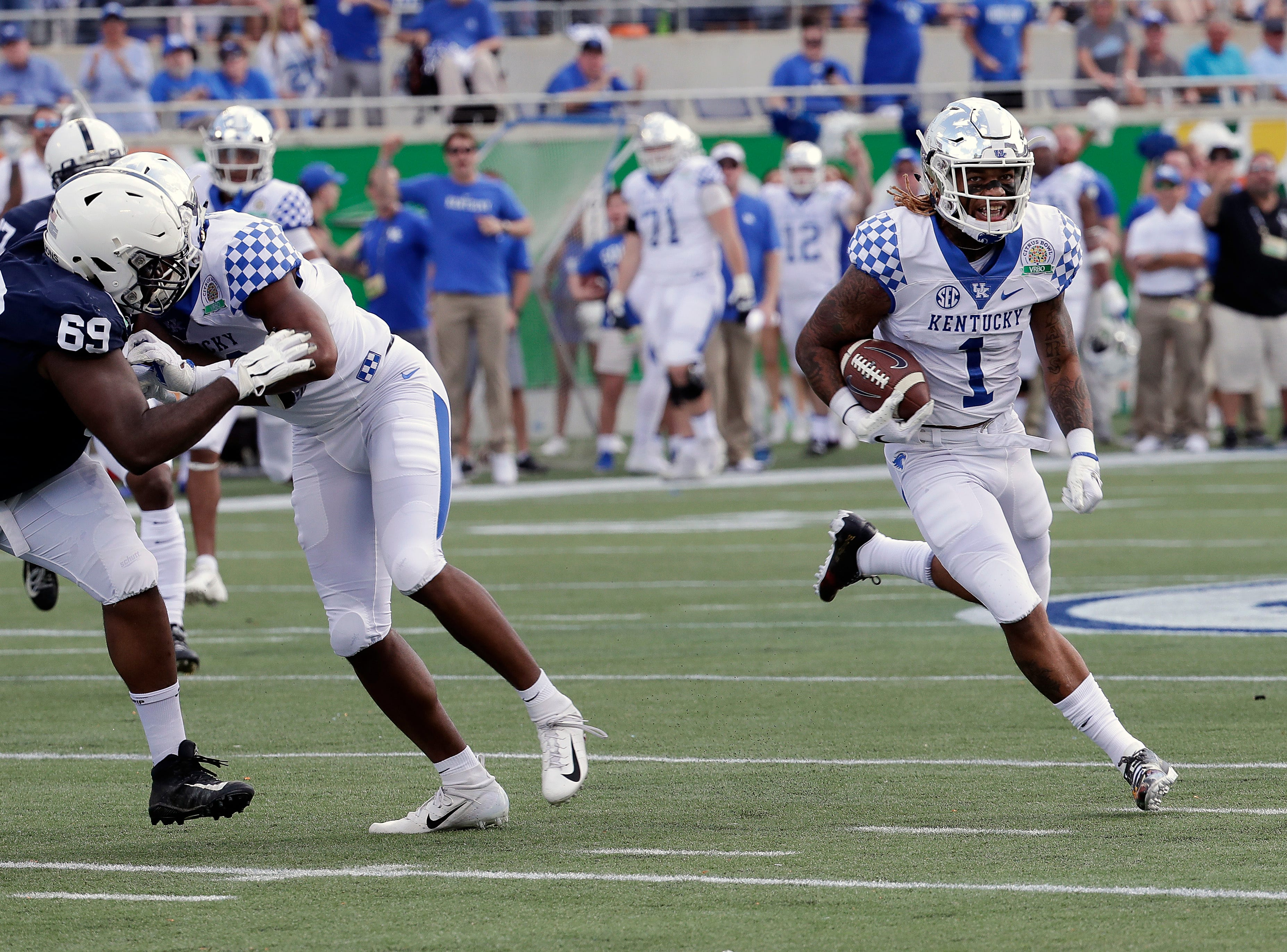 Kentucky's Lynn Bowden Jr. (1) returns a punt for a 58-yard touchdown as he gets past Penn State's C.J. Thorpe (69) during the first half of the Citrus Bowl NCAA college football game Tuesday, Jan. 1, 2019, in Orlando, Fla. (AP Photo/John Raoux)