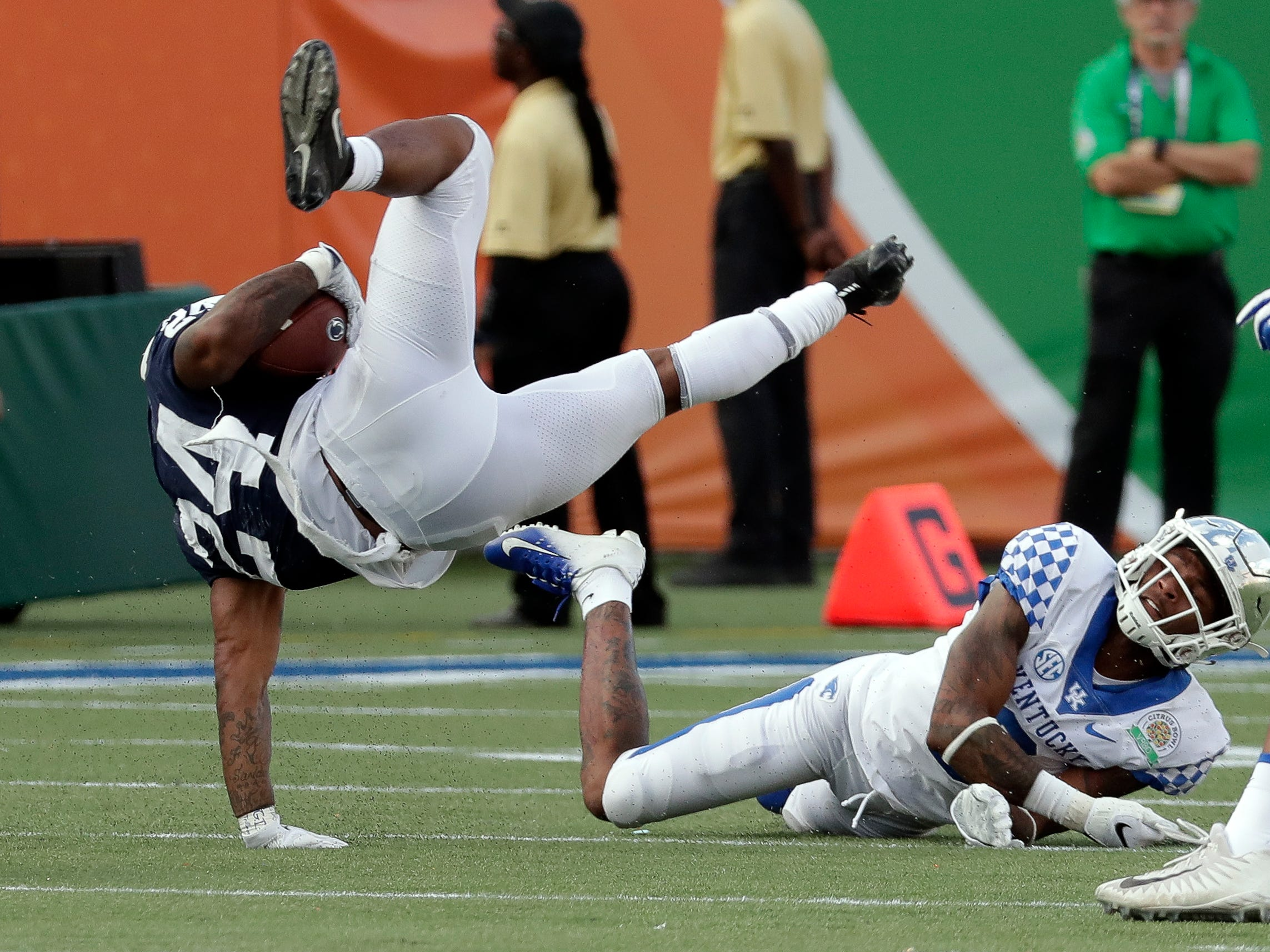 Penn State running back Miles Sanders (24) is upended by Kentucky cornerback Derrick Baity Jr., right, during the second half of the Citrus Bowl NCAA college football game, Tuesday, Jan. 1, 2019, in Orlando, Fla. (AP Photo/John Raoux)