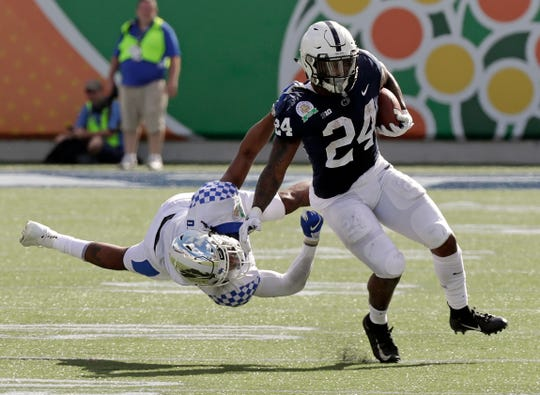 Kentucky safety Davonte Robinson, left, stops Penn State running back Miles Sanders (24) after a short gain during the first half of the Citrus Bowl NCAA college football game, Tuesday, Jan. 1, 2019, in Orlando, Fla. (AP Photo/John Raoux)