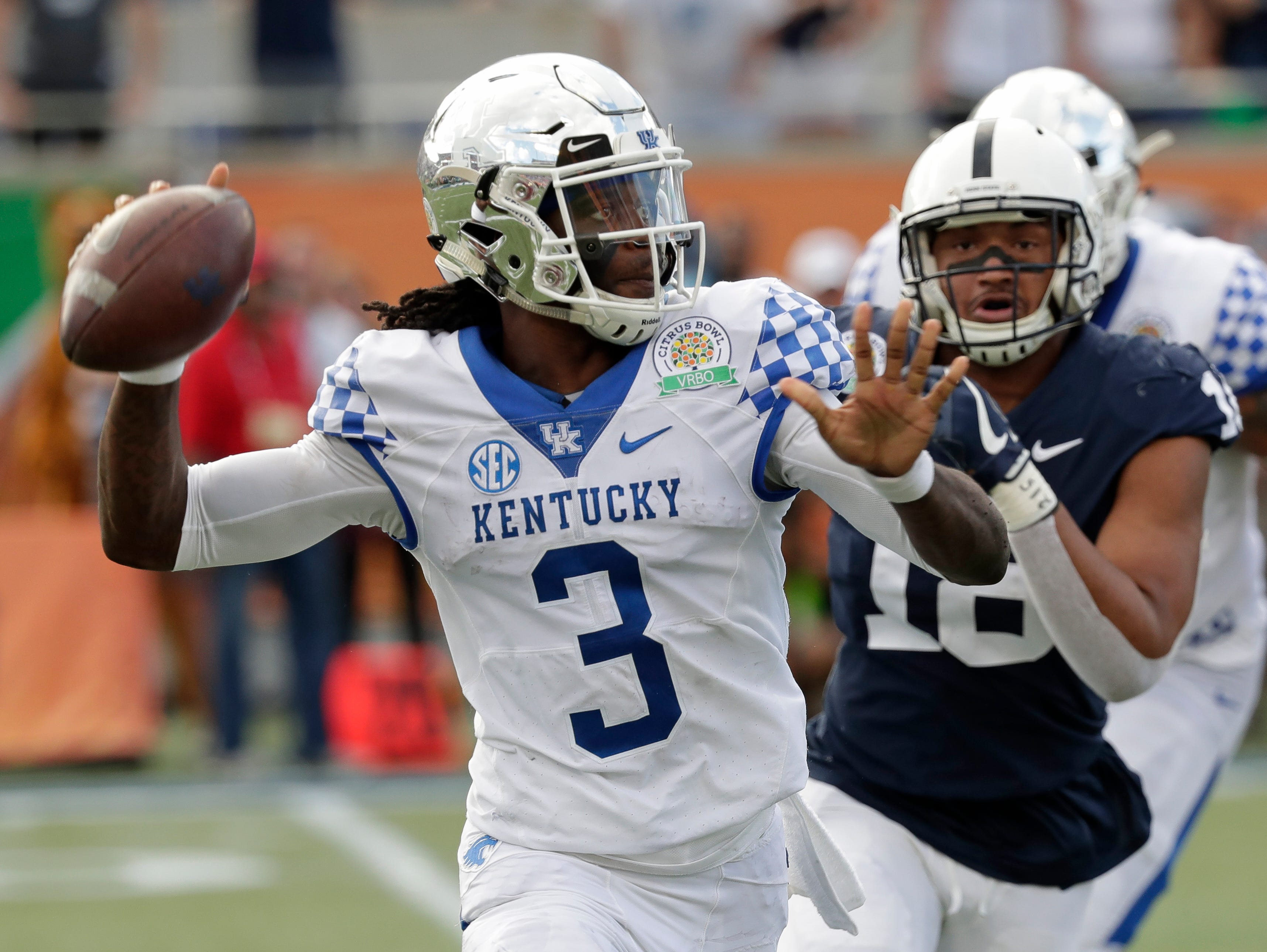 Kentucky quarterback Terry Wilson (3) looks for a receiver as he is pressured by Penn State defensive end Shaka Toney during the second half of the Citrus Bowl NCAA college football game, Tuesday, Jan. 1, 2019, in Orlando, Fla. (AP Photo/John Raoux)