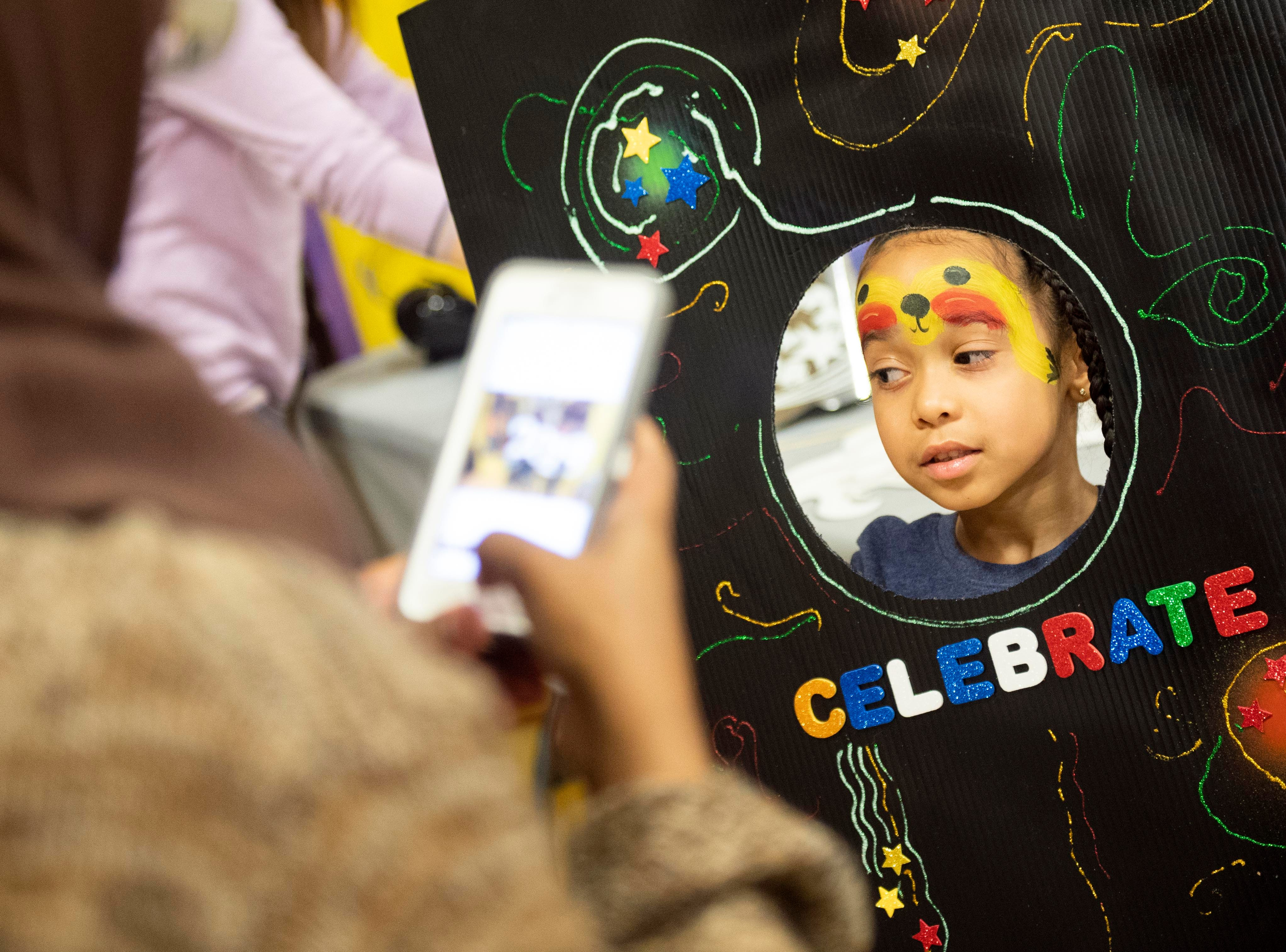 A child sticks her head out of one of the many props avalible for people to take pictures with during the Children's Countdown to 2019 at Voni Grimes Gym, Monday, Dec. 31, 2018. Hundreds of kids rang in 2019 with a balloon drop at 8 p.m.