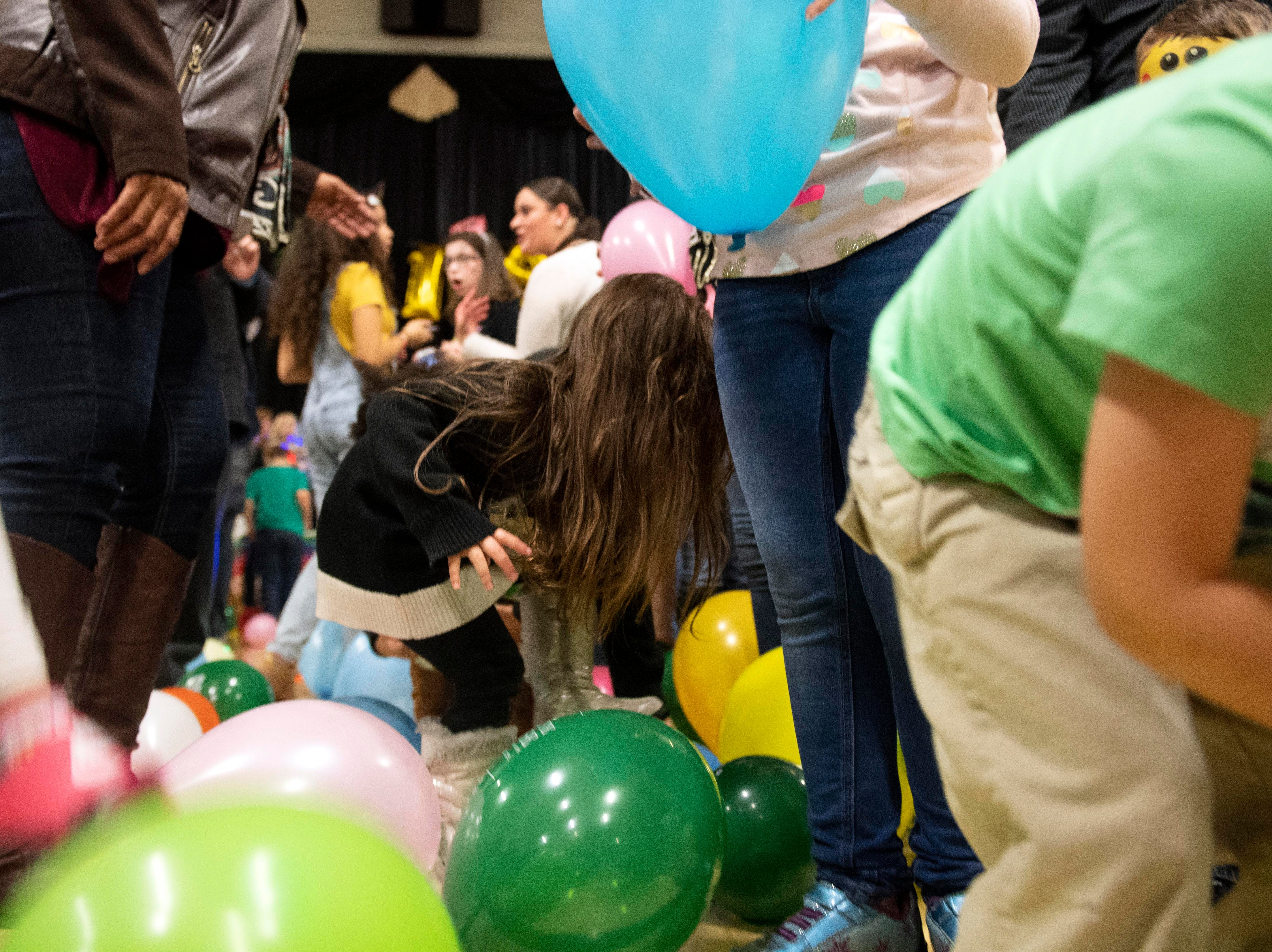After hundreds of balloons drop, children rush to pick them up -- or pop them -- during the Children's Countdown to 2019 at Voni Grimes Gym, Monday, Dec. 31, 2018. Hundreds of kids rang in 2019 with a balloon drop at 8 p.m.