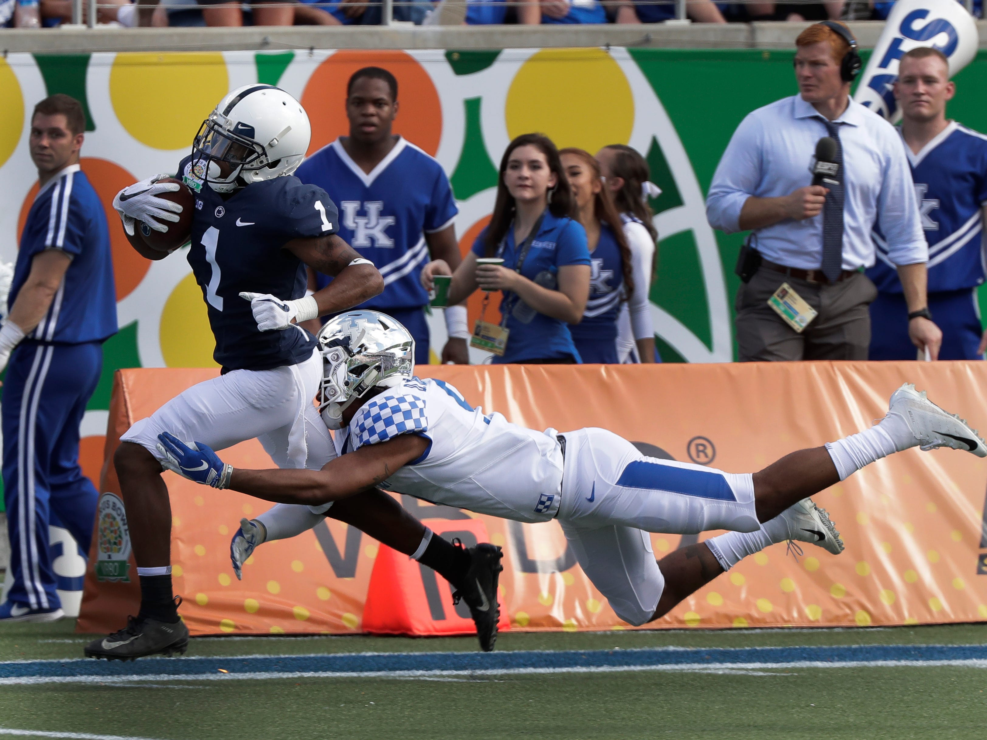 Kentucky safety Davonte Robinson, right, stops Penn State wide receiver KJ Hamler (1) after a 41-yard gain just short of the goal line during the first half of the Citrus Bowl NCAA college football game, Tuesday, Jan. 1, 2019, in Orlando, Fla. (AP Photo/John Raoux)