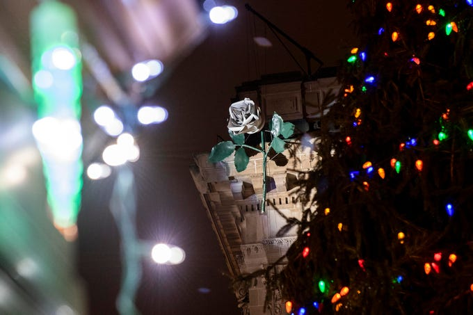 The white rose, prior to dropping, framed by christmas lights in Continental Square downtown, Monday, Dec. 31, 2018. Hundreds gathered to watch the white rose drop, dance and ring in the new year.
