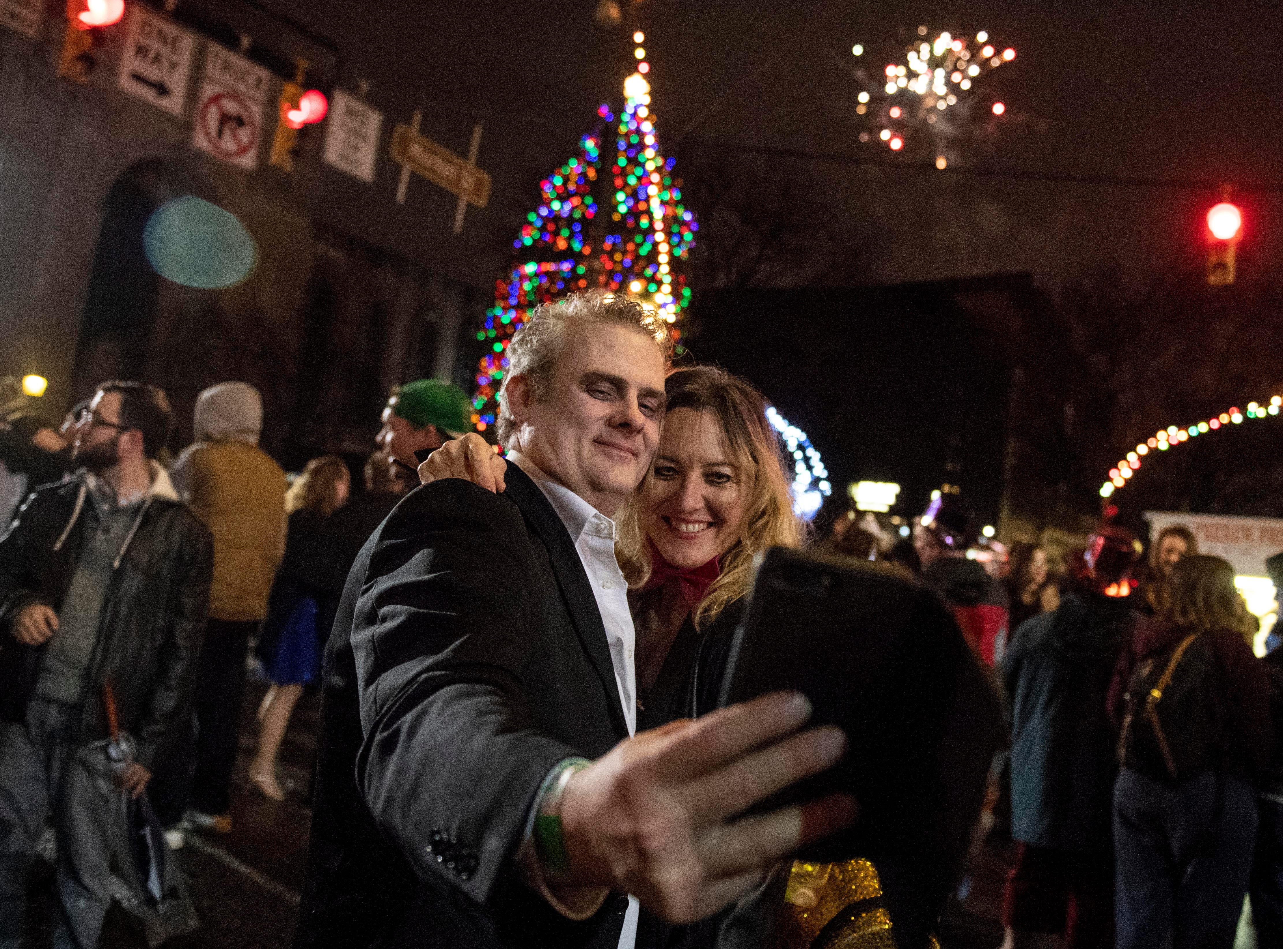 Dennis Hancock, left, and Angela Dumford take a photo as fireworks shoot into the sky behind them after midnight, Tuesday, Jan. 1, 2019, in Continental Square downtown. Hundreds gathered to watch the white rose drop, dance and ring in the New Year.