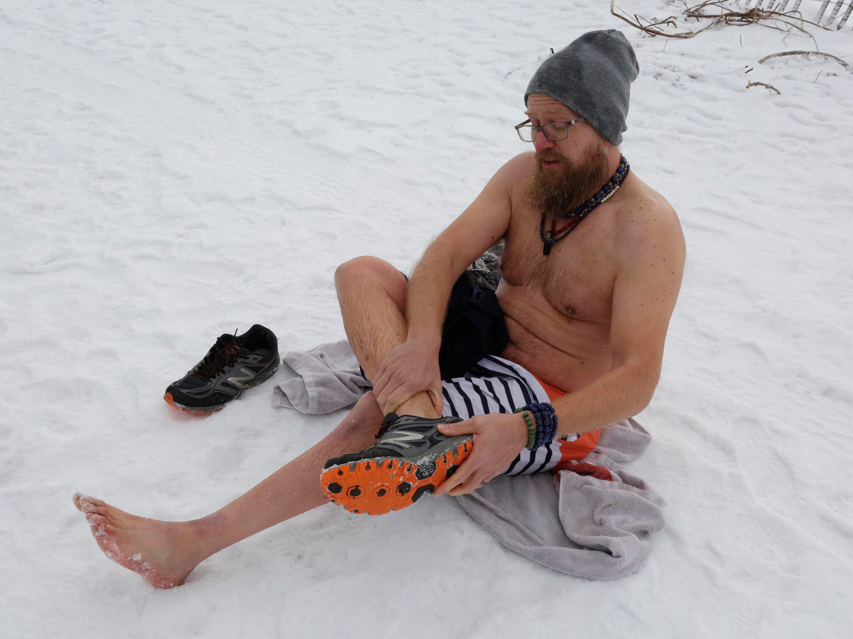 Bryan Reagles of Sheboygan puts on dry socks and shoes after his dip into Lake Michigan, Tuesday, January 1, 2019, at Deland Park in Sheboygan, Wis. He said it was a bit colder than he expected.