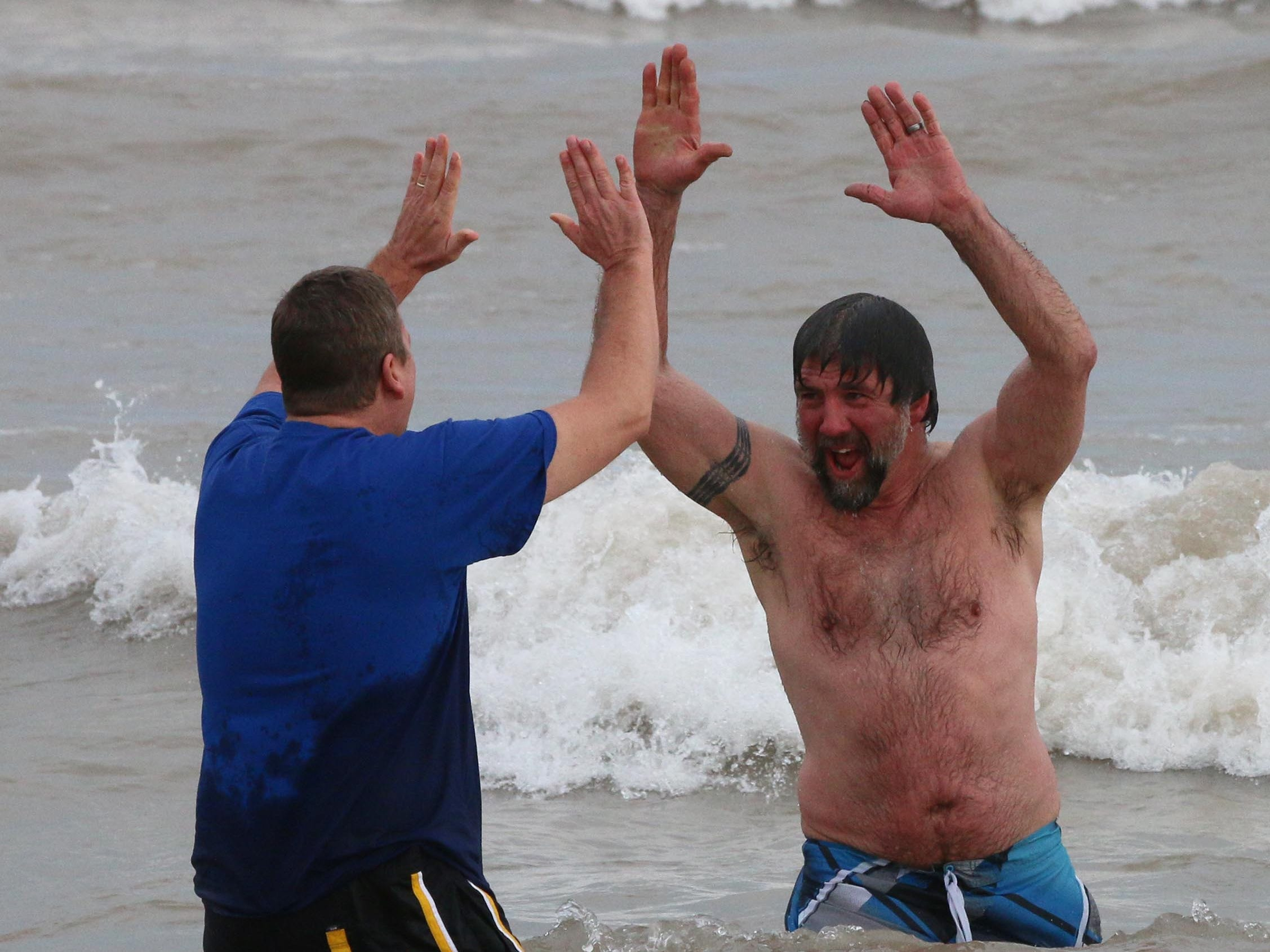 A pair of Polar Bears do a high five during their annual dip into Lake Michigan, Tuesday, January 1, 2019, at Deland Park in Sheboygan, Wis.