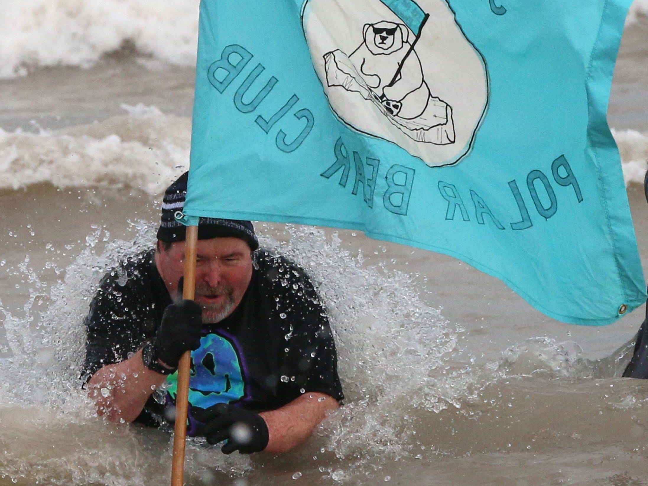 Larry Pratt crests a way while waving the Polar Bear Club banner, Tuesday, January 1, 2019, at Deland Park in Sheboygan, Wis. Pratt said this year was the 49th year of the event as it stretches back to 1971.  He has been doing the dip since 1981.