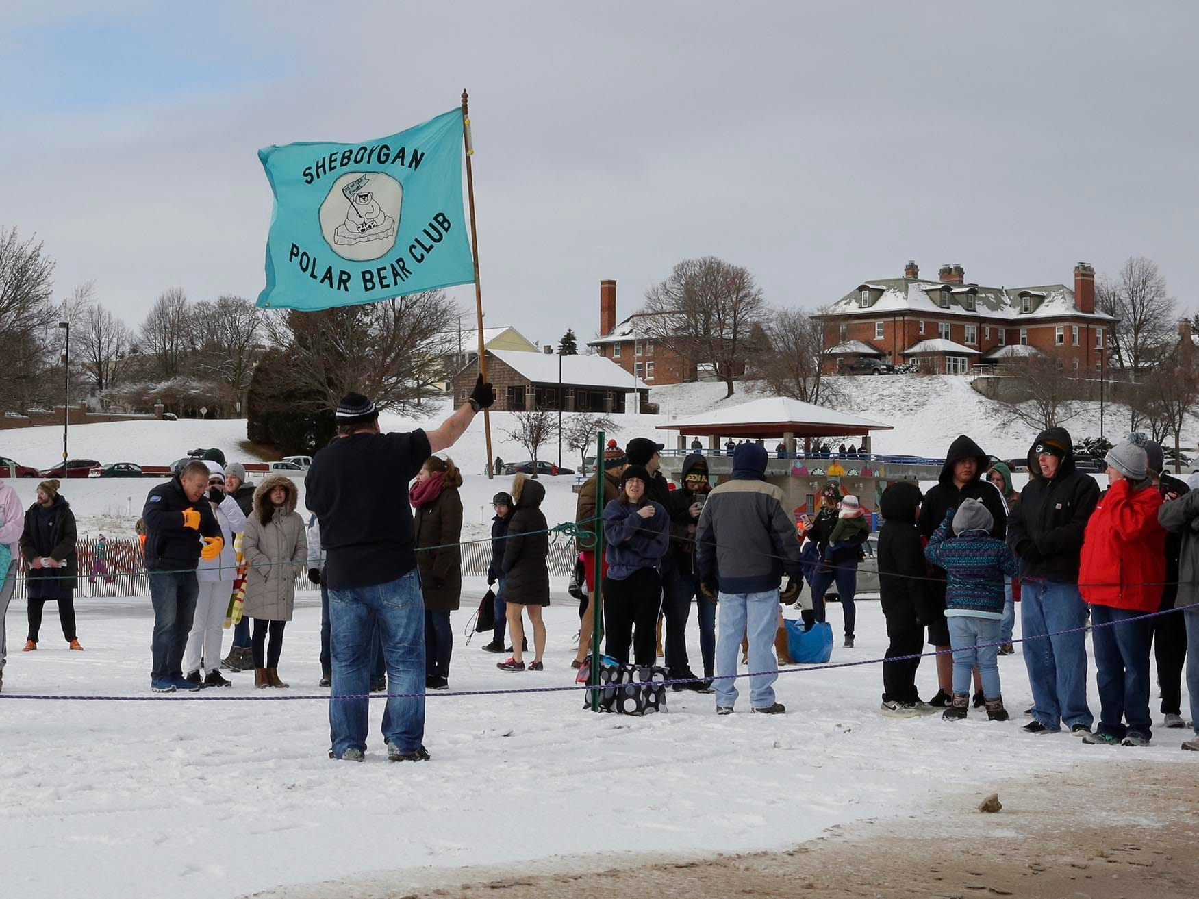 Polar Bear Club's Larry Pratt holds high the club's banner before starting the Polar Bear Dip, Tuesday, January 1, 2019, at Deland Park in Sheboygan, Wis.