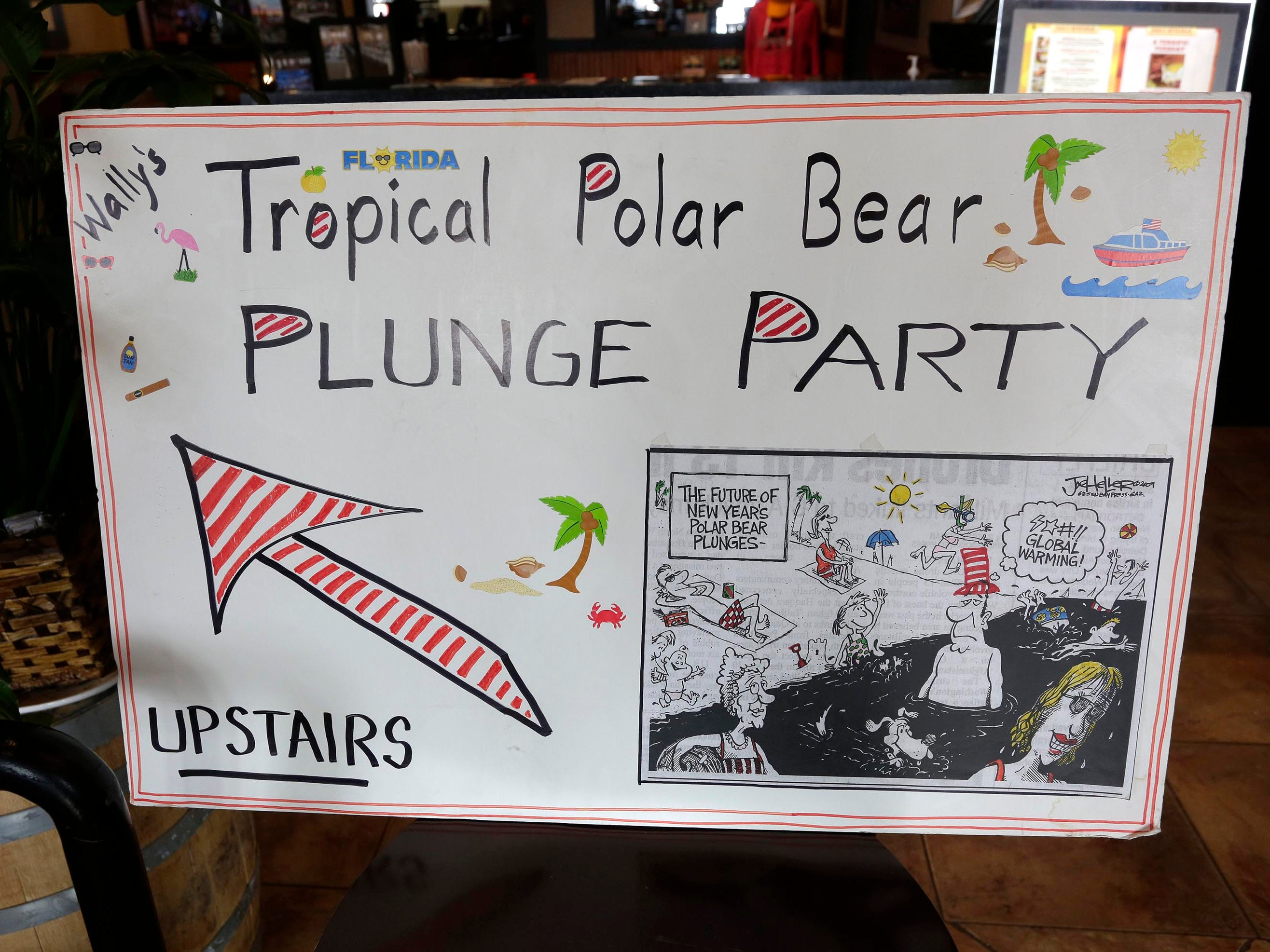 A sign leads the way for Wally Waldhart's Tropical Polar Bear Plunge Party at Sprechers, Tuesday, January 1, 2019, in Sheboygan, Wis.