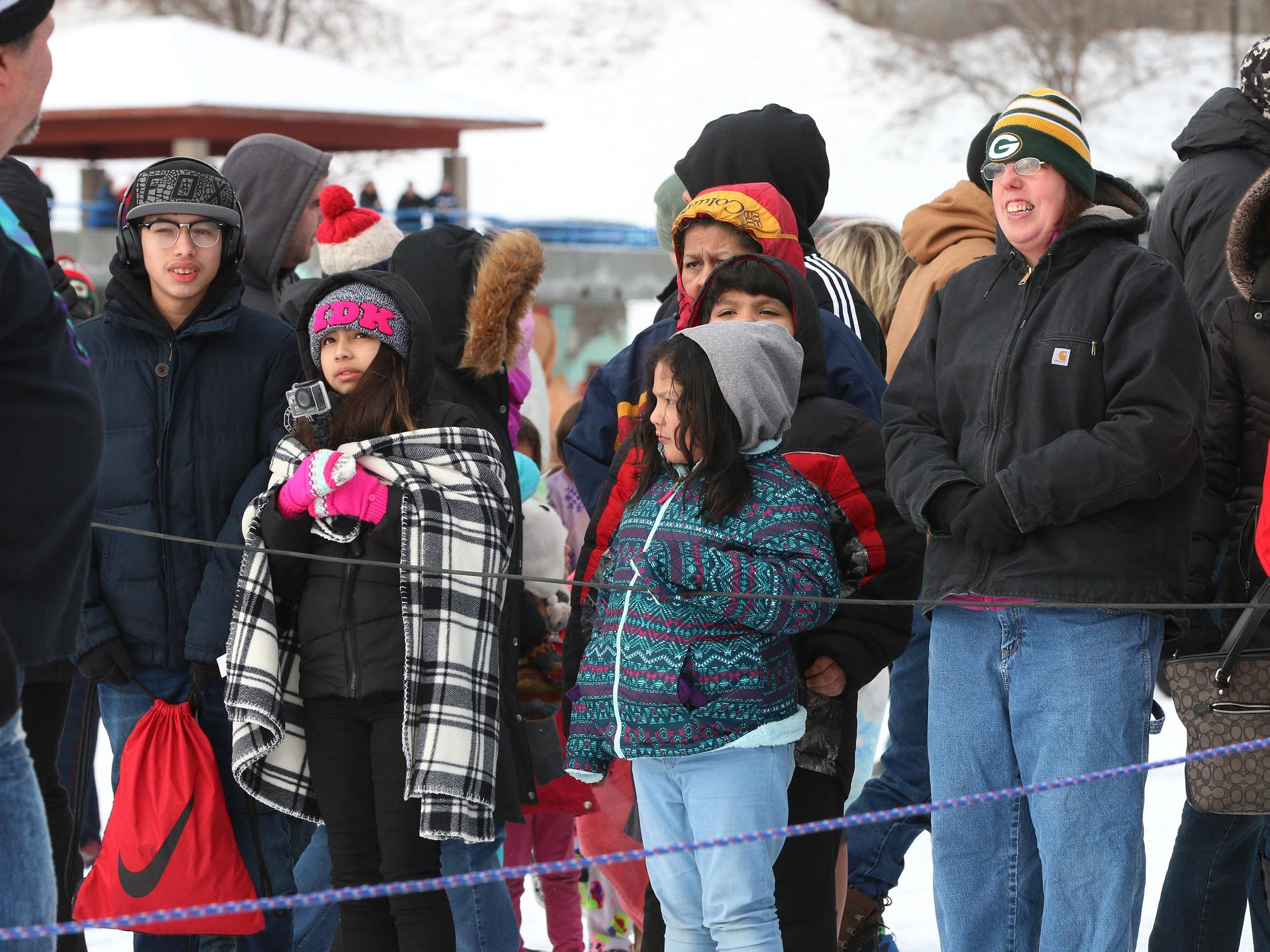 Spectators, dressed warm for the weather wait for the start of the Polar Bear Plunge, Tuesday, January 1, 2019, at Deland Park in Sheboygan, Wis.