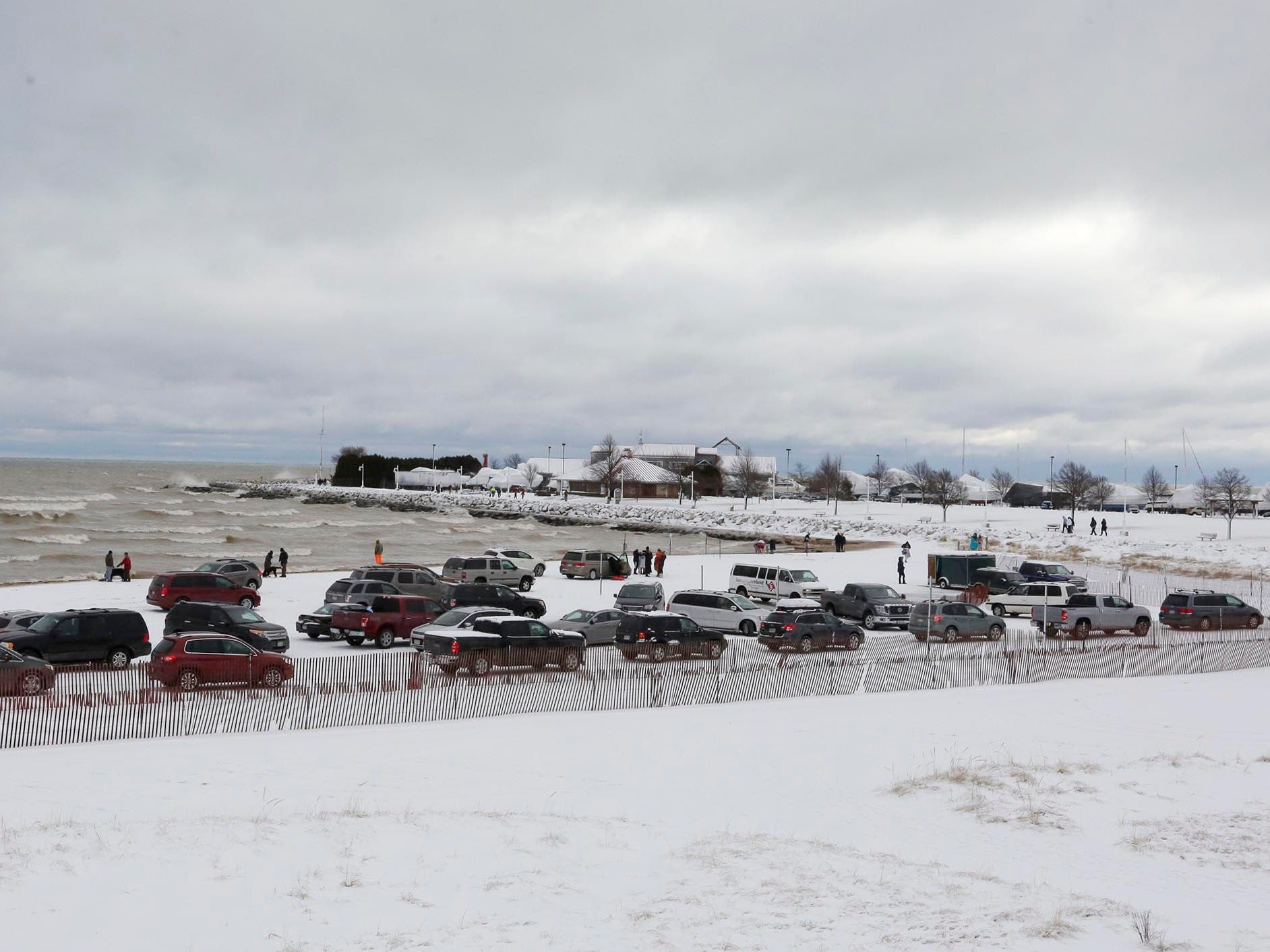 Vehicles line up to leave Deland Park beach following the Polar Bear Plunge, Tuesday, January 1, 2019, at Deland Park in Sheboygan, Wis.